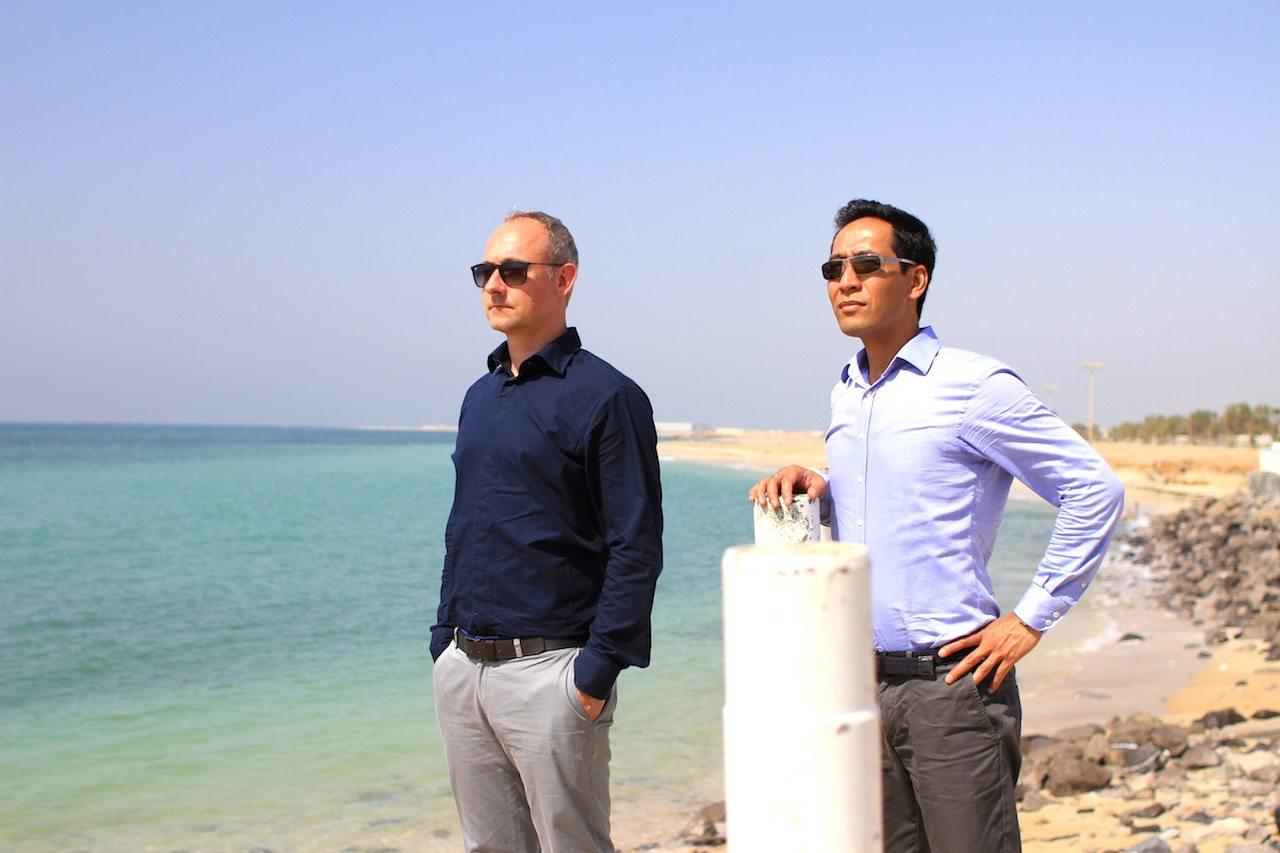 """Die Aussicht:. THE LINK-Gründer Hendrik Bohle (li.) und Jan Dimog am Strand von Umm Al Quwain. Das Emirat war Teil der umfangreichen und mehrmonatigen Recherchen zu unserem """"Architekturführer Vereinigte Arabische Emirate"""" –das Buch mit der Architektur aller 7 Emirate."""