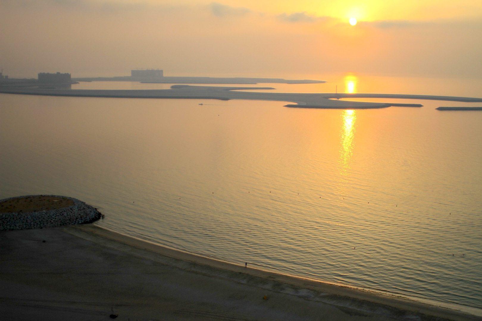 """Sonnenuntergang mit Kunstinsel. Al Marjan Island (""""Koralleninsel"""") ist eine künstlich aufgeschüttete Inselgruppe, auf der eins der touristischen Zentren von RAK hochgezogen wird."""