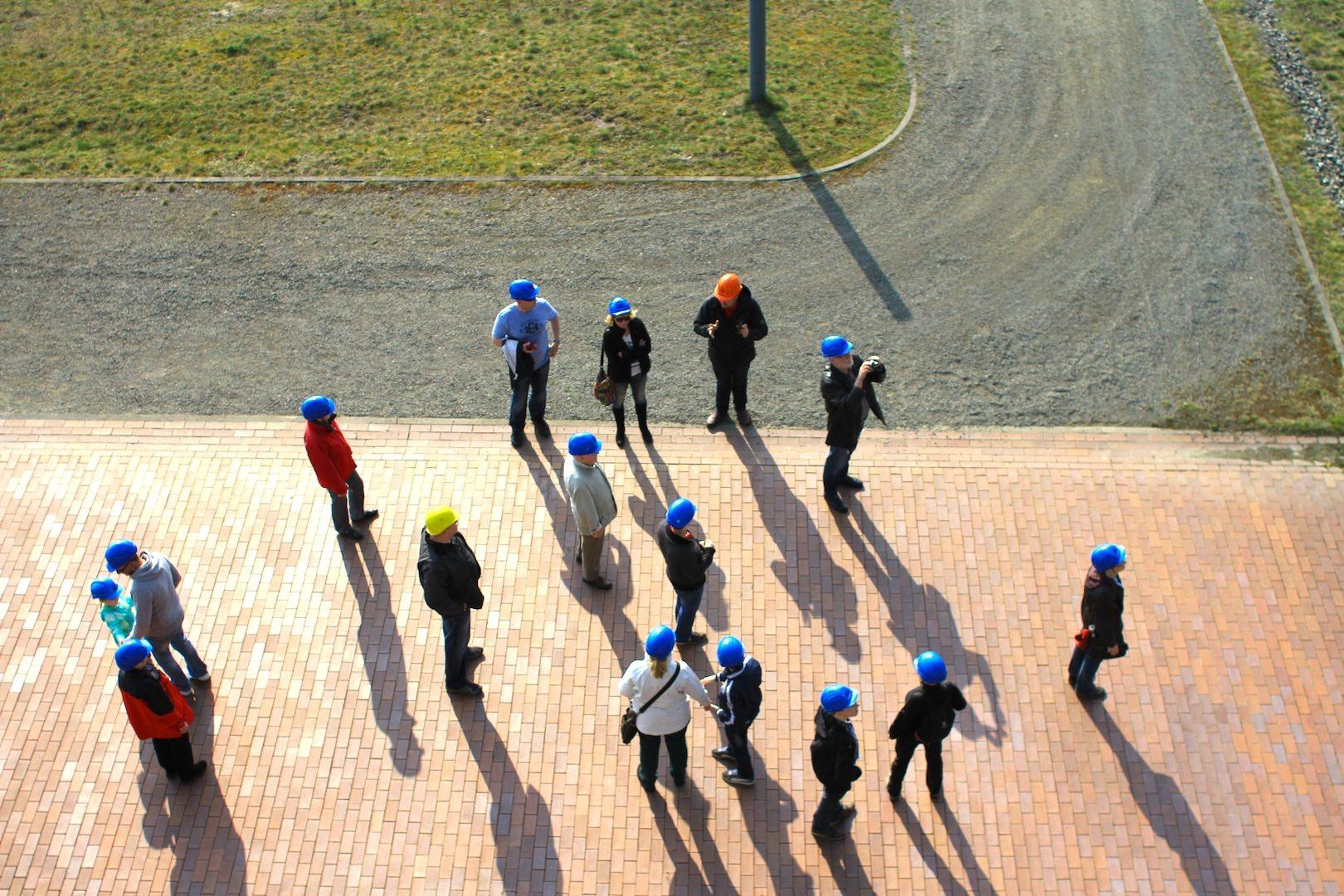 F60. Besucher bekommen gelbe oder blaue Helme, der Tourguide ist orange behelmt.