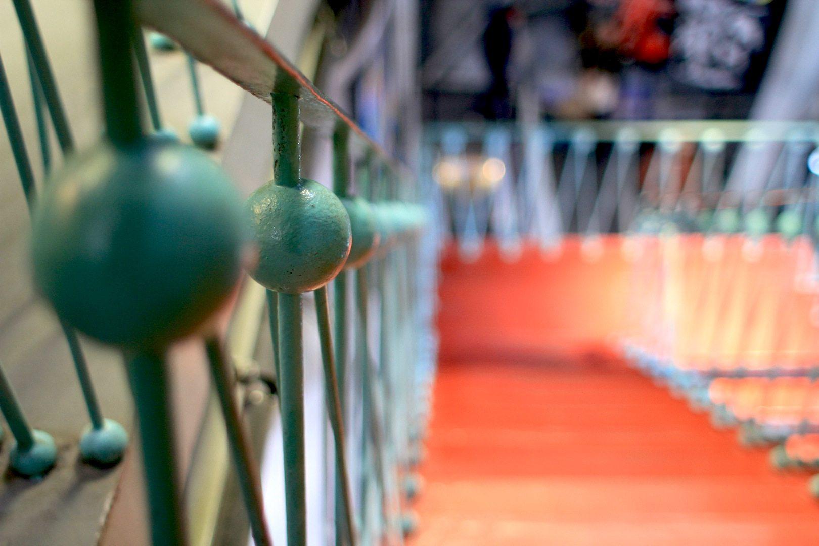 Rot-Türkis. Die roten Treppenläufe mit Geländern in hellem Türkis verbinden (neben den Rolltreppen) nicht nur die Kugeln, sondern auch einzelne Ebenen in den Kugeln.