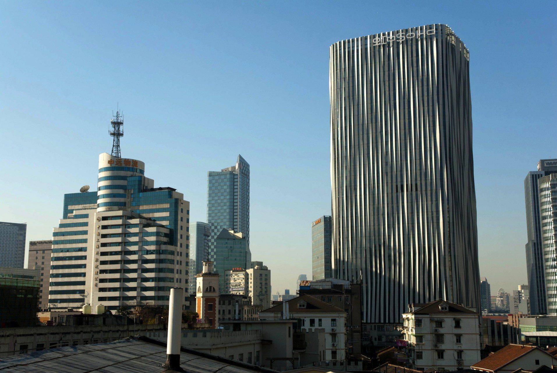 Hongkou SOHO. 2015 – Shanghai, Puxi, Hongkou (Sichuan North Road). Von Kengo Kuma Architects. Das Hongkou SOHO Gebäude ist mit 3D-gewebtem Aluminiumblechen verkleidet, das durch die in sich verdrehte Konstruktion im Lichtspiel wie weiche, sich bewegende Wellen anmutet.