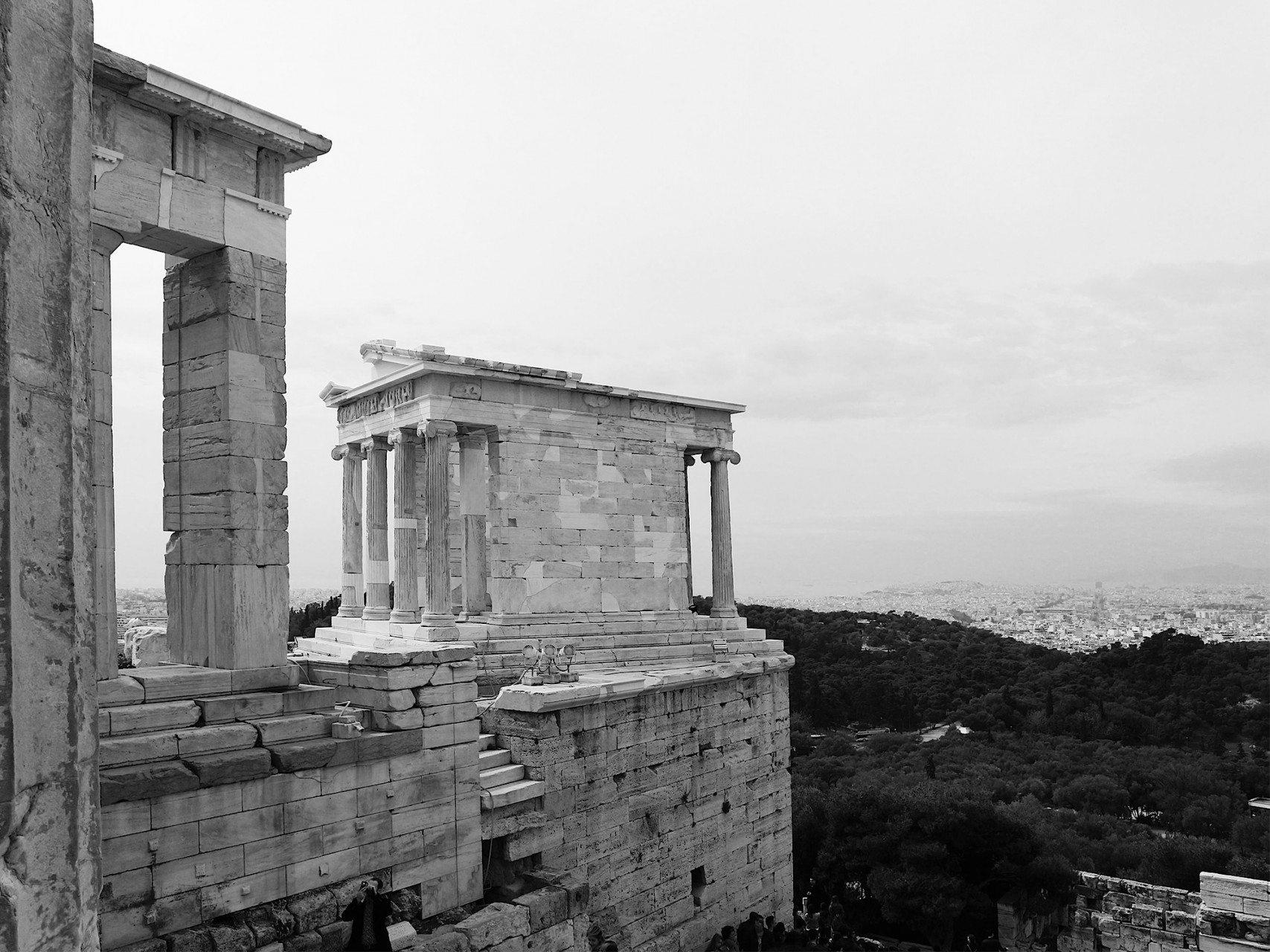 """Der Nike Tempel. Der kleine Tempel steht exponiert auf einer Felszunge unweit der Propyläen. Geweiht wurde er der Kriegsgöttin Nike, die im Kampf gegen die Invasion der Perser den Griechen beiseite gestanden haben soll. Errichtet wurde er zwischen 427 und 425/424 v. Chr. nach Entwürfen des Architekten Kallikrates. Auch die Sieger der Panathenäen, """"der Olympischen Spiele der Antike"""", wurden an diesem Ort geehrt."""