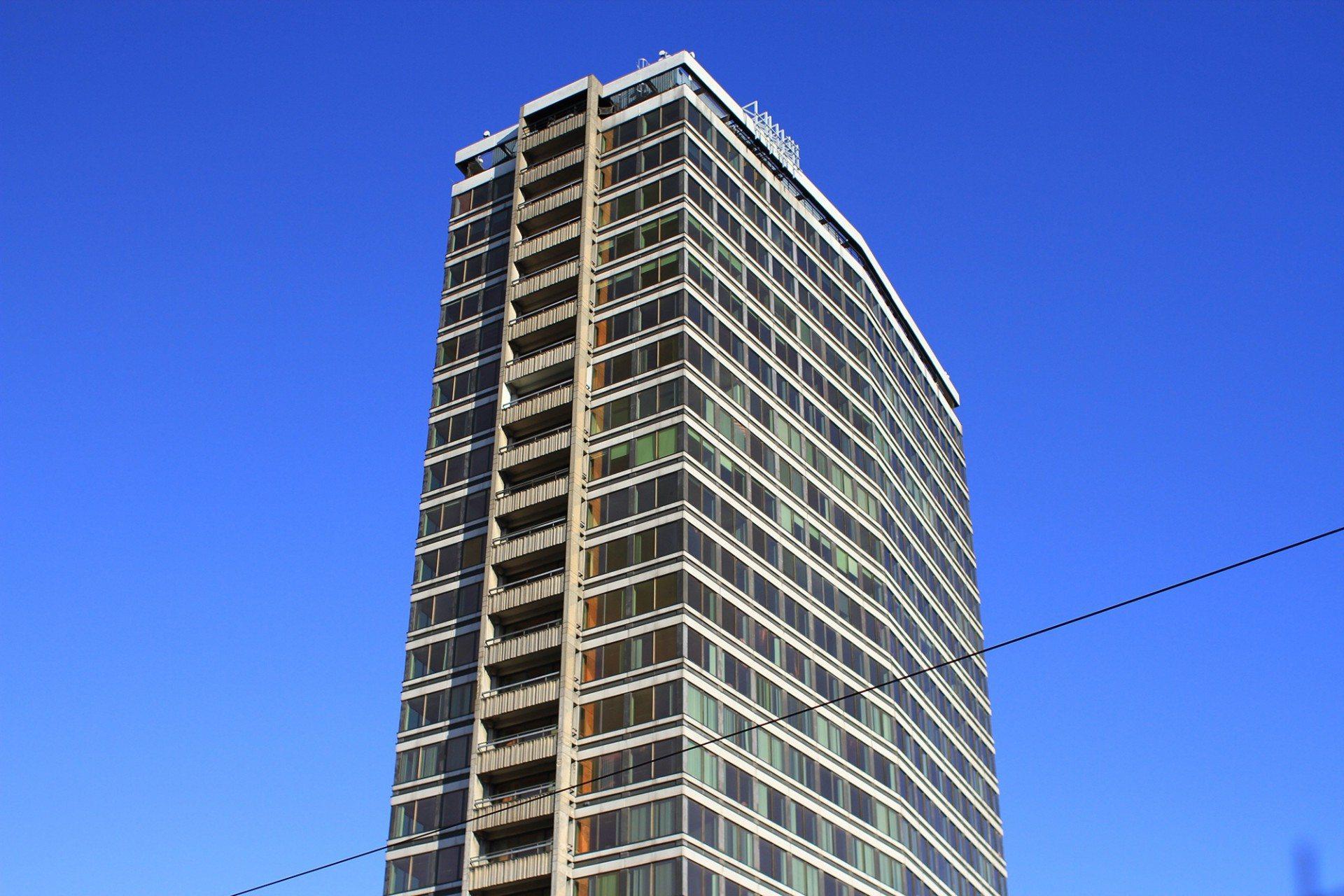 """Geknickt. Der """"Antwerp Tower"""" unweit der Meir, der Flaniermeile der Stadt, wurde 1974 von Conix Architecten und Vincent van Duysen Architects im internationalen Stil errichtet. Mit 87 Metern und 25 Etagen ist er nach der Liebfrauen-Kathedrale (UNESCO-Weltkulturerbe) und dem Boerentoren der dritthöchste Turm der Stadt."""