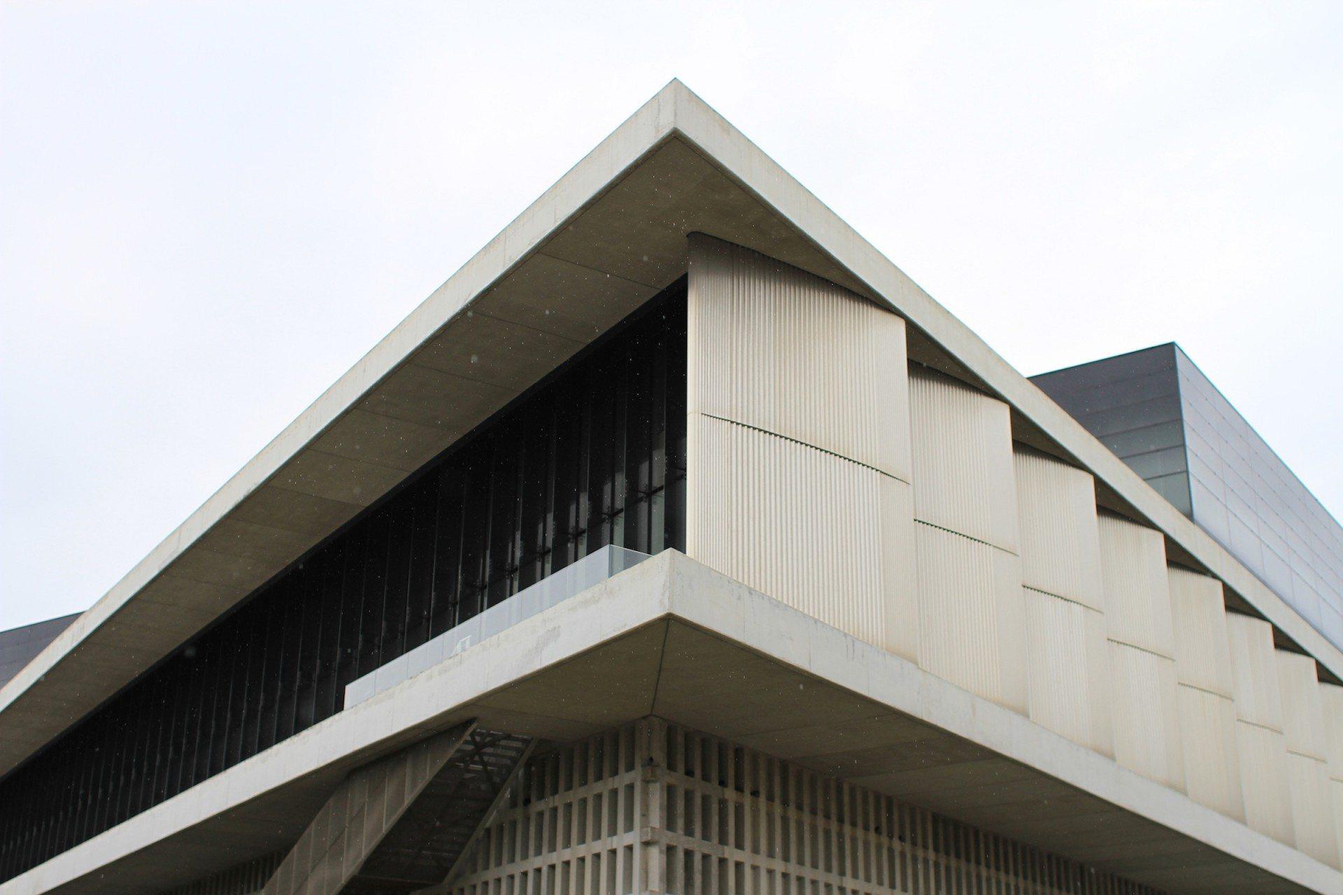 Geschichtet. Die rund um das Gebäude verlaufenden Auskragungen und einfachen Schichtungen verweisen dezent auf eine charakteristische Athener Wohnhaus-Typologie der Nachkriegsmoderne, die sogenannten Polykatoikia.