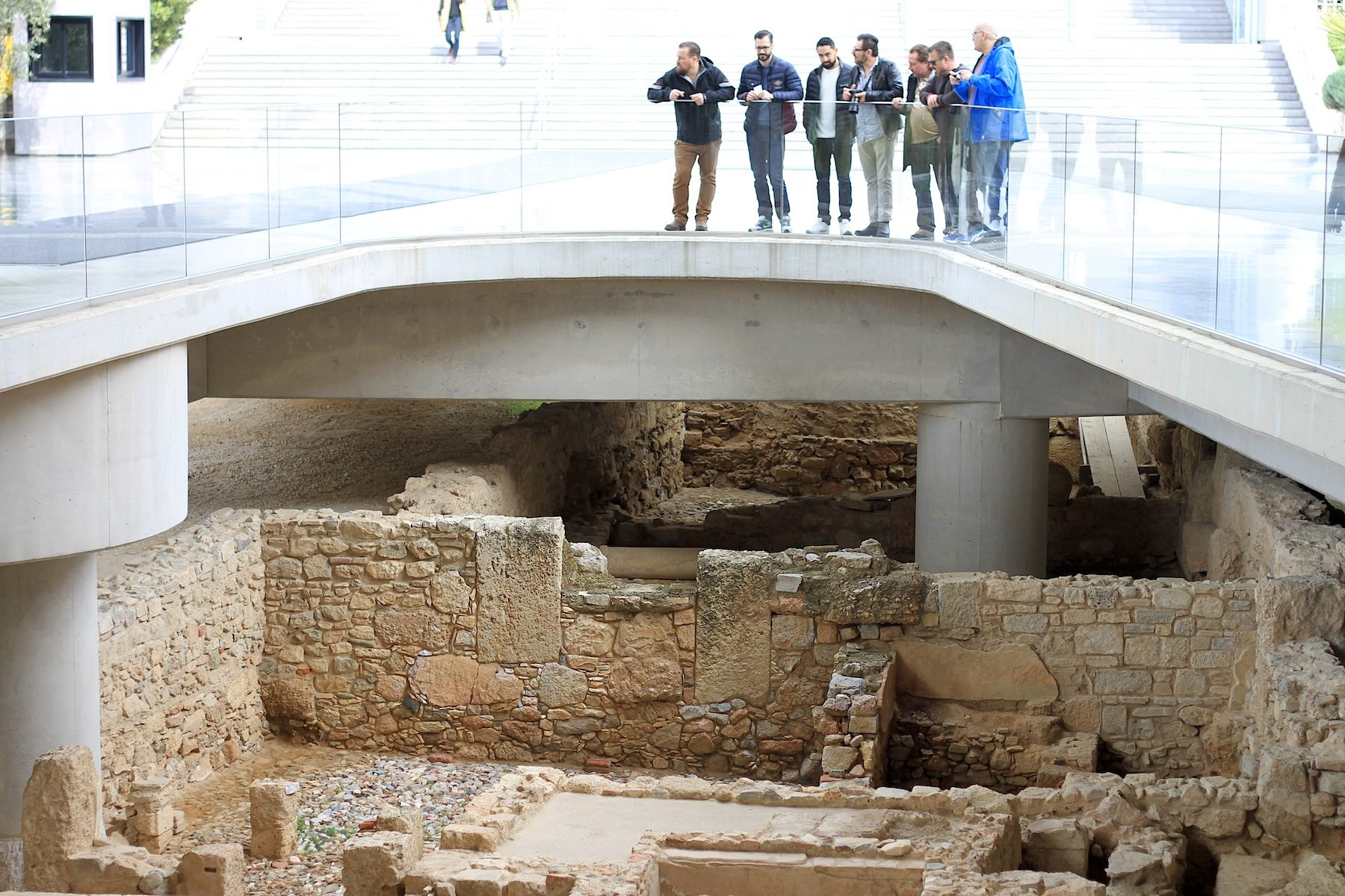 Schwebend.  Das gesamte Gebäude, nicht nur wie hier an der Eingangsrampe, schwebt über der gewaltigen Grabungsstätte eines antiken Stadtbezirks.