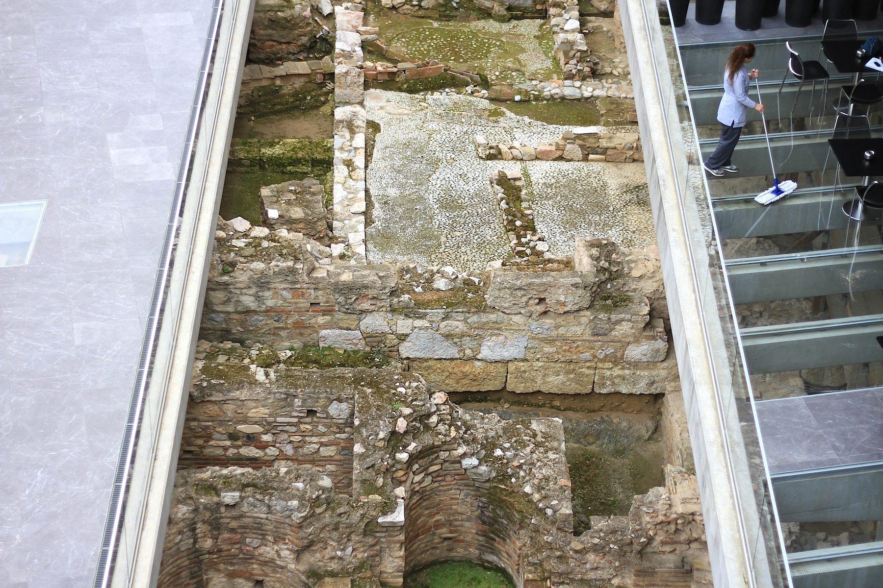 Sichtbar.  Der Ort selbst wird zum Exponat. Große gläserne Bodenplatten erlauben immer wieder Blicke auf die archäologischen Schätze der Stadt.