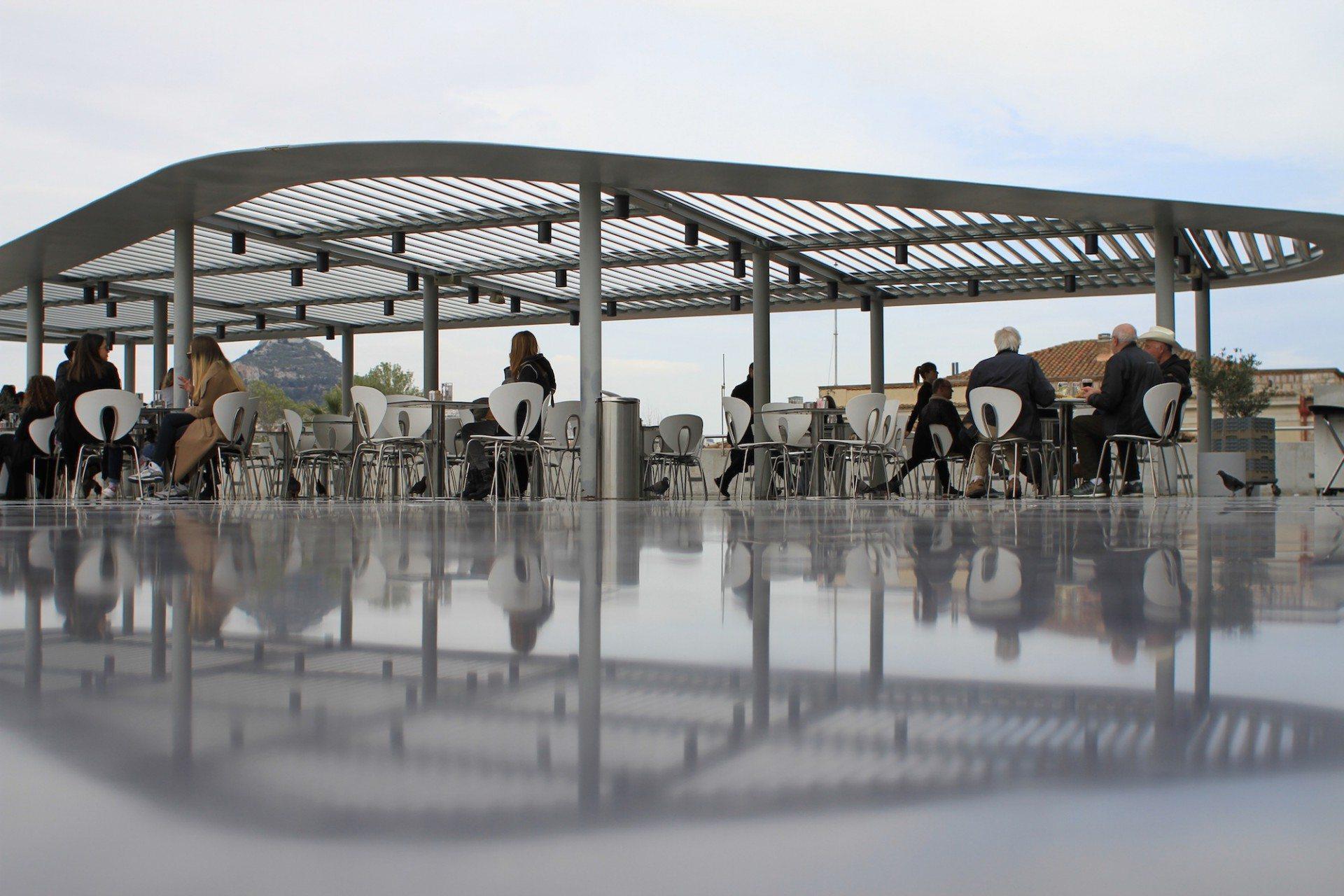 Überdacht.  Direkt über der Haupteingangsrampe befindet sich das Café mit einer teils überdachten Terrasse mit Blick auf die Akropolis. Sie ist eine Anspielung auf die in Griechenland weit verbreiteten überdachten Innenhöfe.