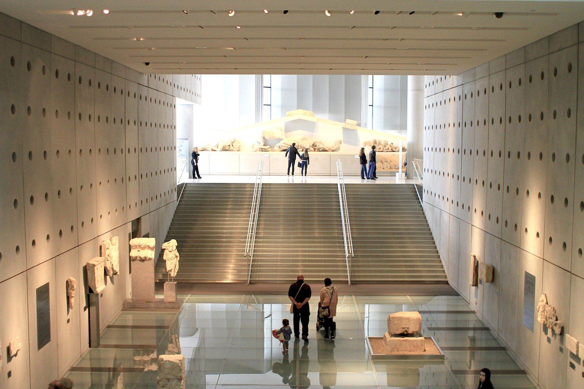 Aufsteigend. Eine gläserne Rampe und marmorne Freitreppe führt in den oberen Ausstellungssaal. Der Rundgang soll an den beschwerlichen Aufstieg auf den Tempelberg erinnern. Dieses Gefühl wird durch den Wechsel der Raumhöhe von fünf Metern auf das Dreifache verstärkt.