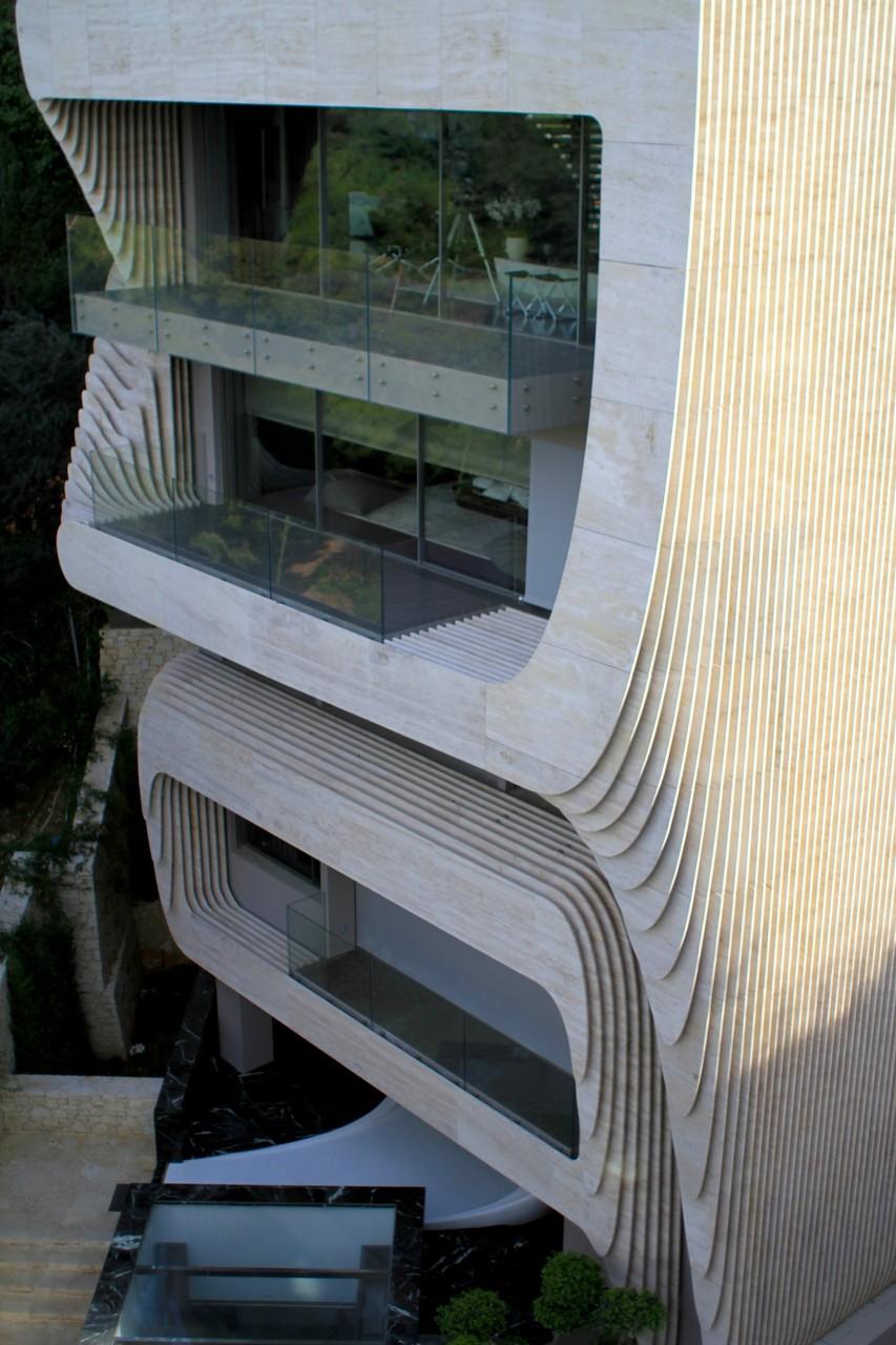 Solospiel.  Das One Kleomenous des griechischen Architekturbüros Omniview. Die auffällige Hülle besteht aus Travertin und nimmt mit seiner Form Bezug auf die Böschungs- und Schutzmauern des Lykavíttos.