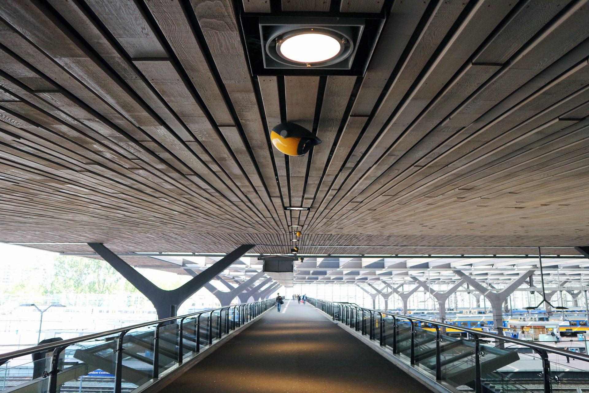 Centraal Station. Gedreht gespiegelte Y-Stützen tragen das luftige Bahnhofshallendach über den Gleisen. Am gespreizten Sockel führen Treppen ins Erdgeschoss.
