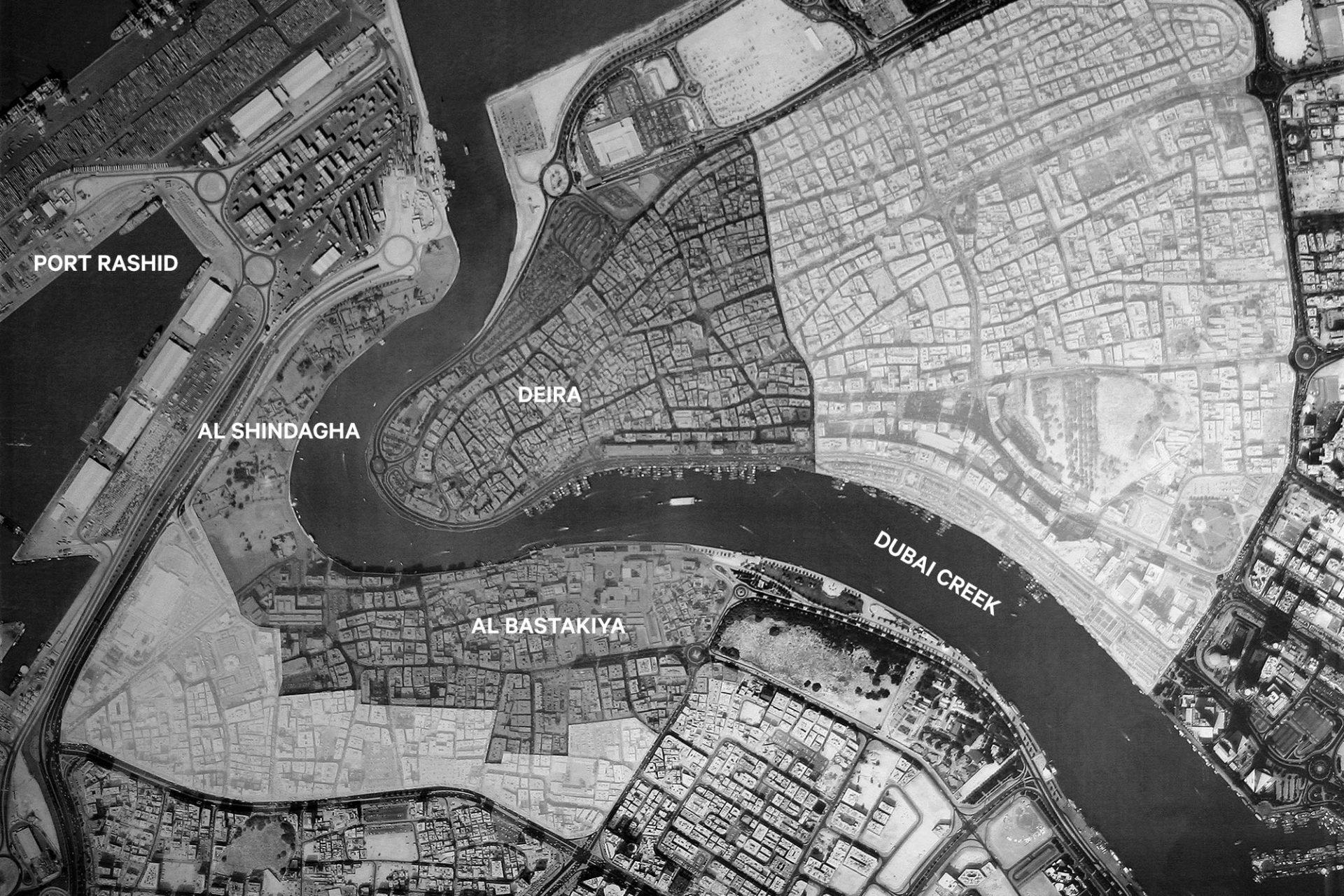 """Dubai. Der Creek mit Deira im Westen, Al Shindaya im Osten und Al Bastakiya im Süden. Der Hafen """"Mina Rashid"""" wurde künstlich aufgeschüttet und 1972 eröffnet."""