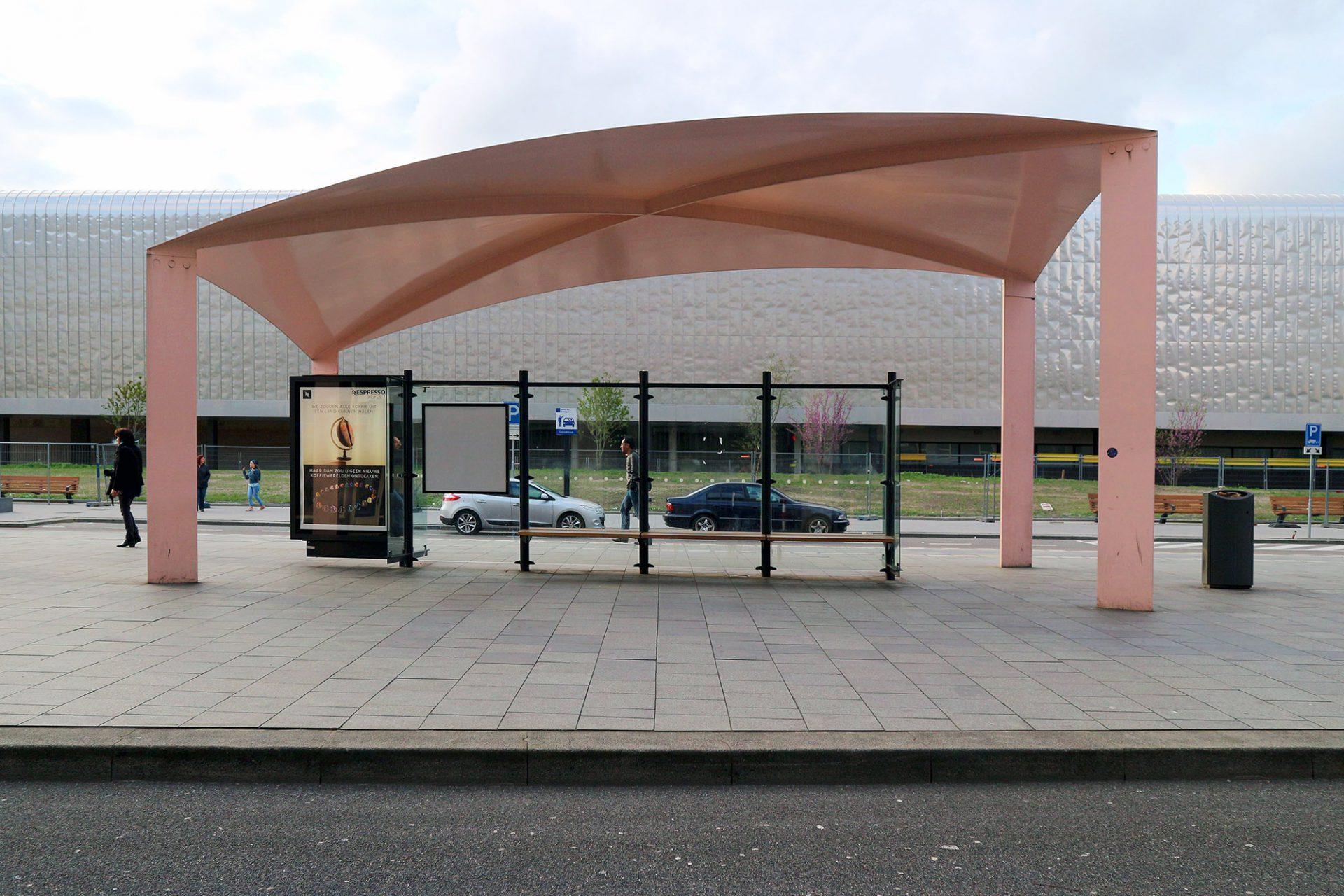 Busstation. Eine Windböe scheint die feinen Stahldächer aufzublähen.