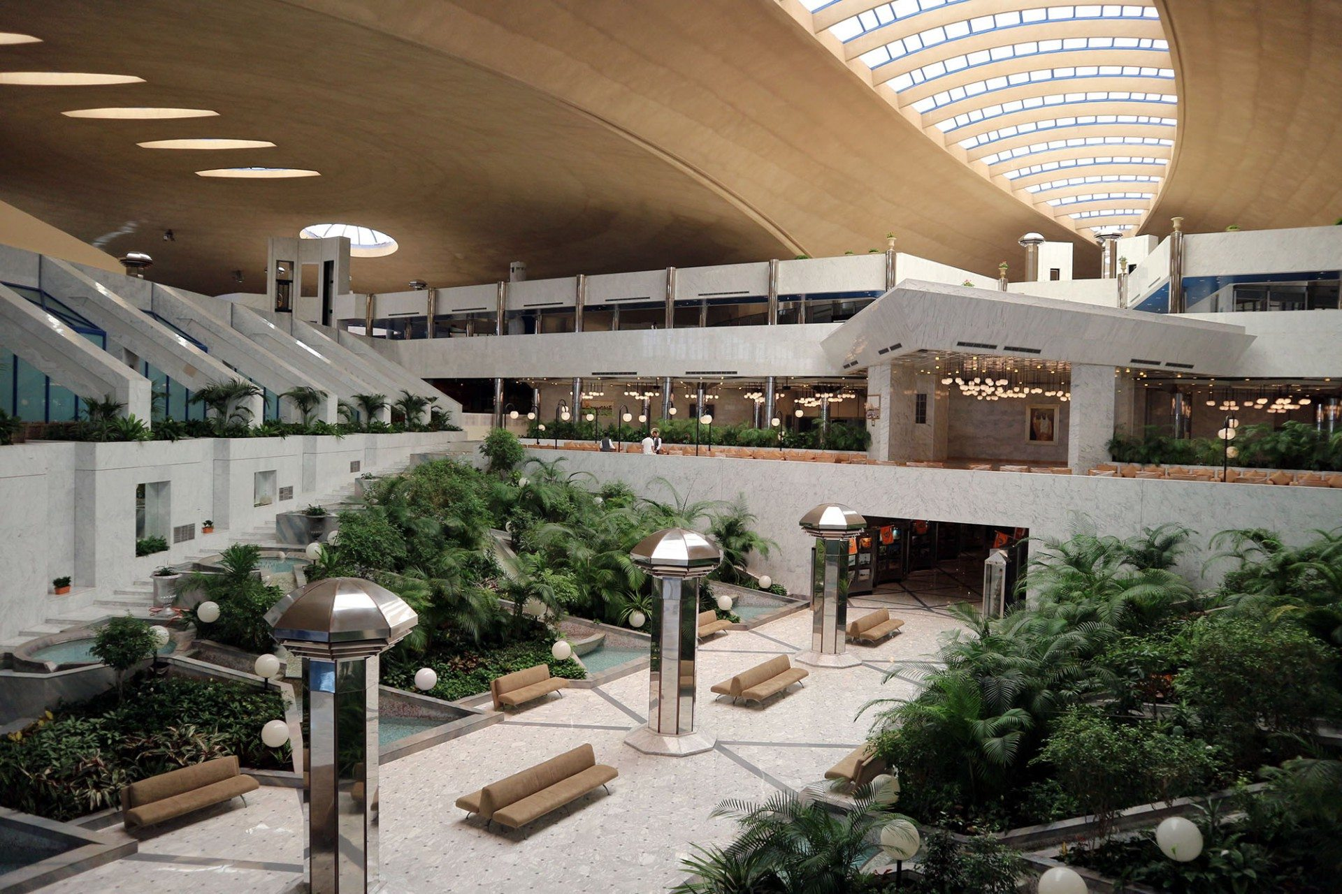 Metaphorisch.  In Anlehnung an die Oasenstadt liegen den Naturstein verkleideten Konferenzformationen grüne Gärten und falaj-ähnliche Wasserspiele zu Füßen.