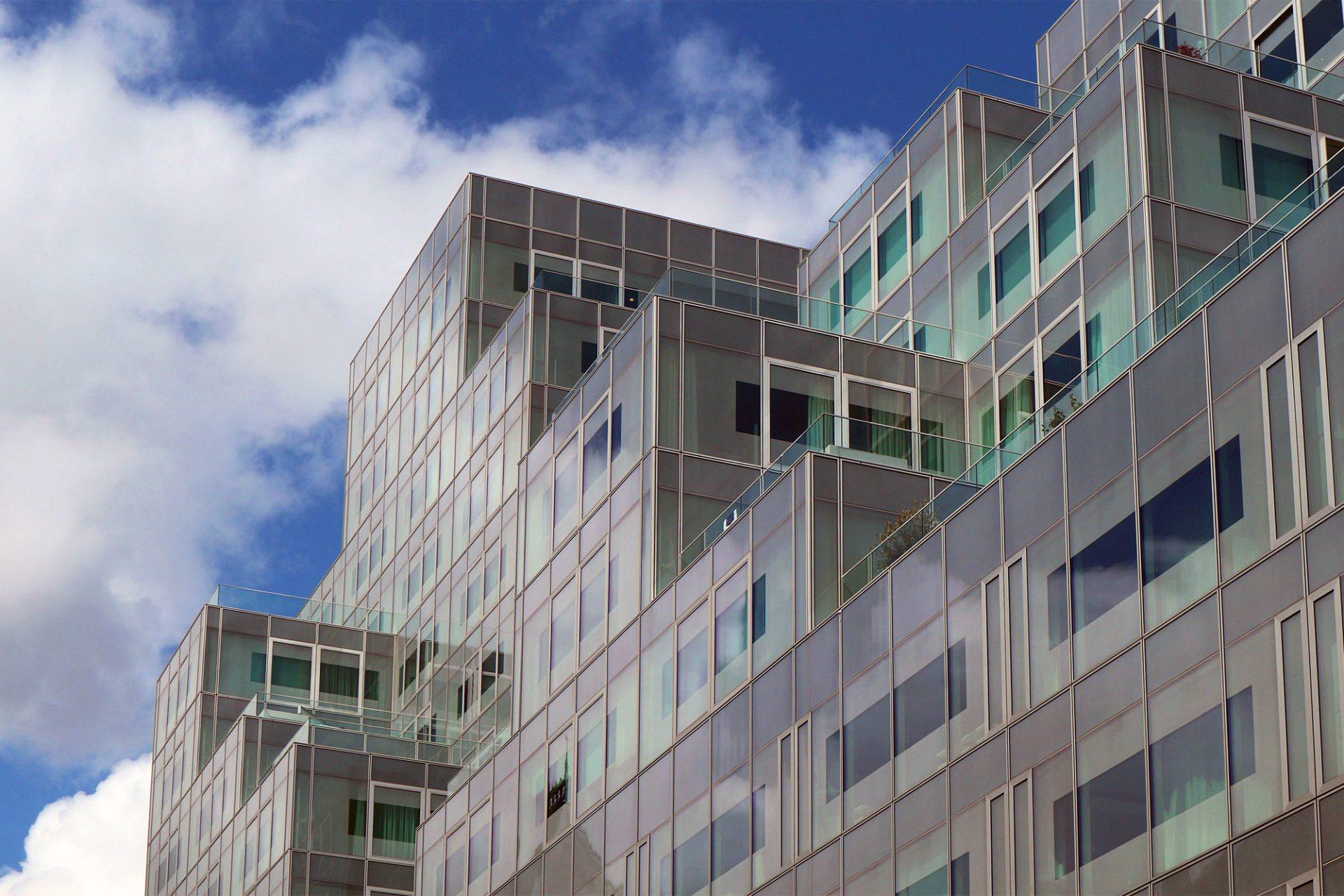 Timmerhuis. Die Fassade spiegelt den Himmel und schimmert in Blau- und Grauabtönungen.
