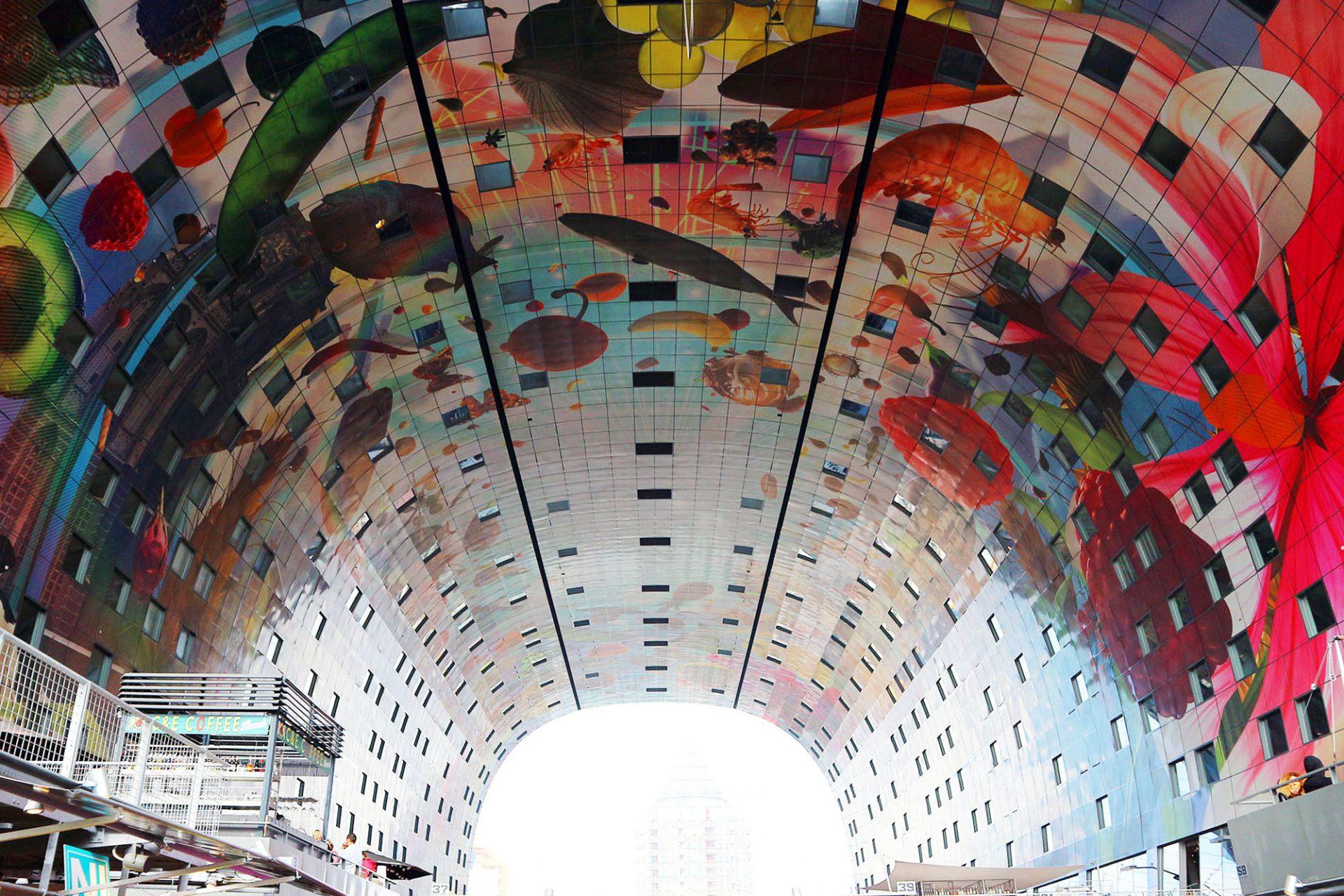 Markthal. Ein quietschbuntes Kunstwerk von Arno Coenen und Iris Roskam verschönert den Innenraum. Abgebildet sind Produkte, die an den Ständen zum Verkauf stehen.