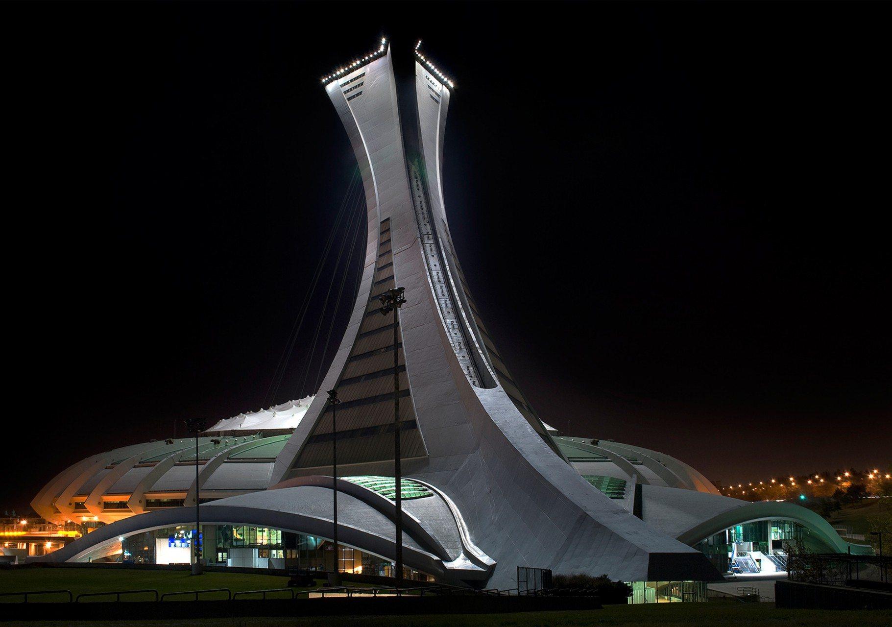"""Stade Olympique Montréal.  Zusammen mit dem renommierten Stuttgarter Ingenieurbüro Schlaich Bergermann & Partner realisierte Taillibert das Olympiastadion in Montréal. Der Bau wurde damals kontrovers diskutiert, sprengte er bei seiner Errichtung 1997, wie viele andere Olympiaprojekte, bei weitem den anvisierten Kostenrahmen. Dennoch bescheinigte die """"Zeit"""" dem Bauwerk seinerzeit, es sei """"ein Festival fürs Auge"""". Sein wandelbares Kevlar-Membrandach ist eines der ersten und größten weltweit, das vollständig aus Kunststoffen konstruiert wurde. Die 20.000 qm Membranfläche wird von einem 168 m hohen, leicht geneigten Turm an Seilen abgelassen. 43 Winden, 26 Aufhängepunkte und 17 Randseile, die am Betonkranz verankert sind, halten sie in seiner antiklastischen (gegenseitig gekrümmten) Form. Das Dach kann in nur 30 Minuten vollautomatisch entfaltet werden. Eine zusätzliche PVC-Membran, welche mittels eines Kevlar-Seilnetzes unter die Haupt-Membran gespannt wird, schützt vor den kalten kanadischen Wintern. Auf der Spitze des prägnanten Turmes befindet sich der Salon Montréal, der bis zu 200 Personen aufnehmen kann. In verglasten Doppeldecker-Gondeln werden die Besucher über eine Seilbahn bis zu der auf 166 Meter gelegenen Aussichtsplattform fördert."""