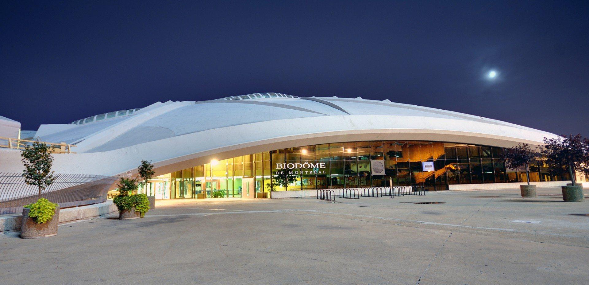 """Biodôme de Montréal.  Östlich des Stadions befindet sich das ehemalige olympische Velodrom. Der gewaltige Schalenbau wurde ebenfalls von Roger Taillibert entworfen. Während der Spiele 1976 diente er neben den Radsportwettbewerben auch den Judowettkämpfen als Austragungsort. Nach umfangreichen Renovierungsmaßnahmen zwischen 1989 und 1992 befindet sich hier heute das Umweltmuseum """"Biodôme"""". In Simulationen präsentiert es verschiedene Ökosysteme: das tropische Südamerika, den Laurentinischen Wald Nordamerikas, den Sankt-Lorenz-Strom sowie die beiden Polargebiete Arktis und Antarktis."""