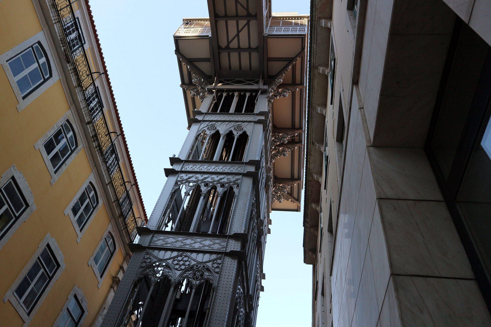 Elevador de Santa Justa.  Die vertikale Struktur besteht aus dem Metallturm, einer Aussichtsplattform, einem Gehweg und der Basis, die aus vier Säulen besteht.