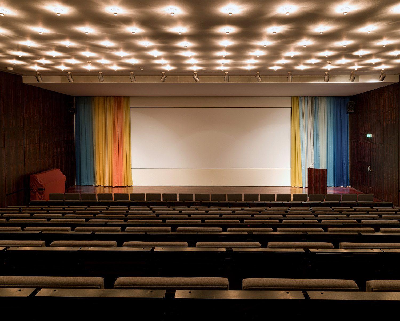 """Das Auditorium.  Der Vorhang mit dem Titel """"Colors from Canaan"""" des Konzept-Künstlers Olaf Nicolai hängt seit 2013 auf der Bühne des Saals im unteren Geschoss."""