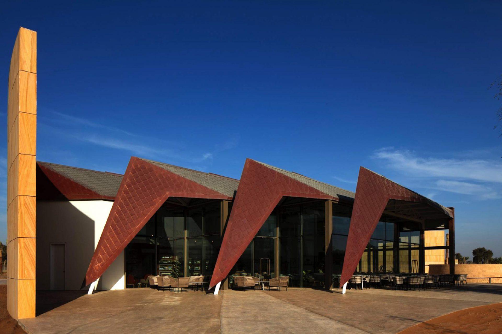 Mleiha Archaeological Centre. Das Café am Ende des Ausstellungsrundgangs ist großzügig verglast. Dachdeckung und Sonnenschutz aus Kupfer verweisen auf die antiken Kupferwerkstätten, die es hier einst gab.