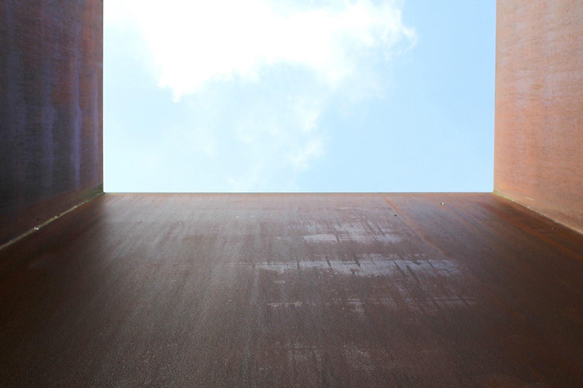 """""""Axis"""".  Die Skulptur des amerikanischen Künstlers Richard Serra neben dem Haupteingang wurde 1989 aufgestellt. Drei gewaltige, etwa 10 Meter hohe Scheiben aus Corten-Stahl scheinen gegeneinander gelehnt. So entsteht der Eindruck eines fragilen Gleichgewichts."""