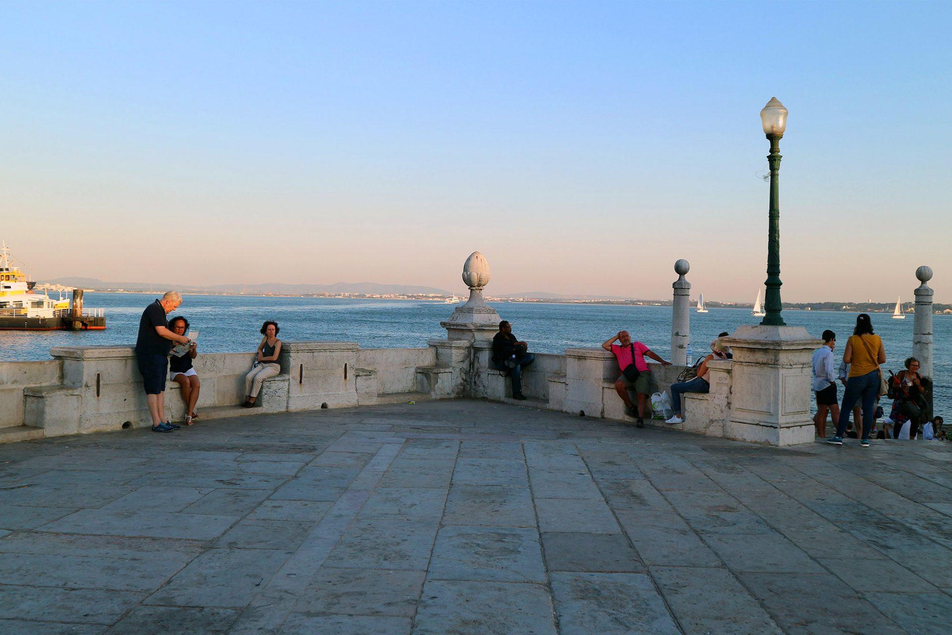 Cais das Colunas.  Zwei große Säulen flankieren eine marmorne Rampe, die zum Wasser führt. In die steinernen Ballustraden sind Sitze eingelassen (blaue Metro, Terreiro do Paço).