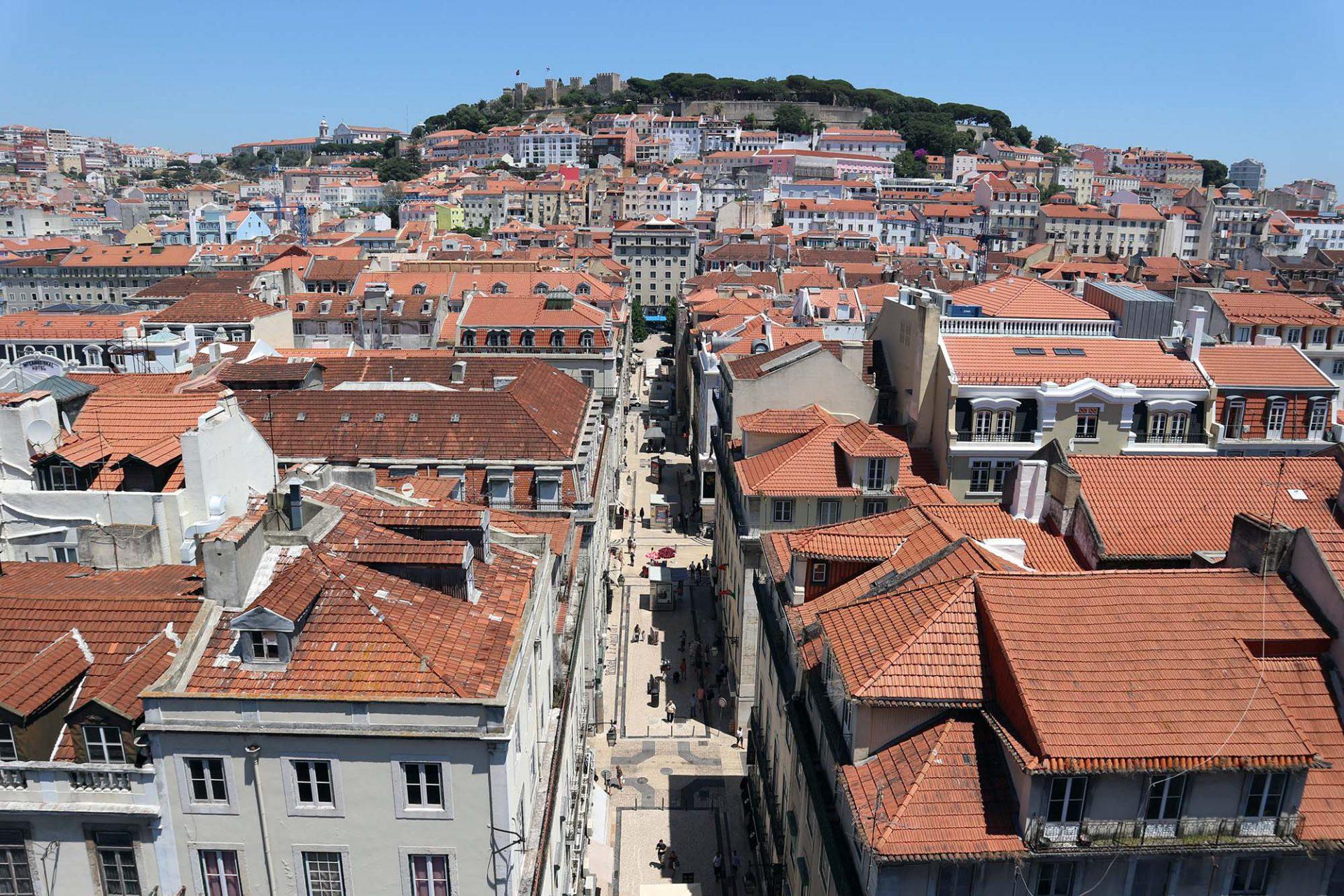 Miradouro Elevador de Santa Justa.  ... den Kirchtürmen, Kuppeln und ziegelgedeckten Dächern der Viertel Mouraria und Alfama und die Bastionen des Castelo de São Jorge auf der gegenüberliegenden Erhebung.