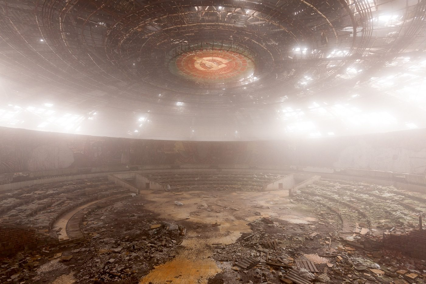 Innenraum bei aufziehender Bewölkung. Das Buzludzha-Denkmal auf dem Gipfel des 1.441 Meter hohen Berges Chadschi Dimitar wurde 1981 nach den Plänen des Architekten Georgi Stoilow errichtet. Das anlässlich des 1.300-jährigen Jubiläums der Staatsgründung Bulgariens errichtete Denkmal umfasst einen Kongressaal, der umlaufend mit realsozialistischen Mosaiken verziert ist, einen mit ebensolchen verzierten Außengang sowie einen 115 Meter hohen Turm, dessen rote Sterne einst beleuchtet und weithin sichtbar waren. Seit dem Ende der sozialistischen Herrschaft in Bulgarien steht das Denkmal leer und ist Verfall und Vandalismus ausgesetzt.