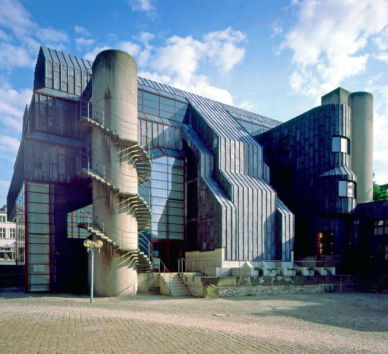 Der Anbau.  Die ursprünglich großen Glasfronten mussten wegen zu starker Klimaschwankungen und zu großer Helligkeit geschlossen werden. Im Anbau wurde die Klimatechnik eingebaut.