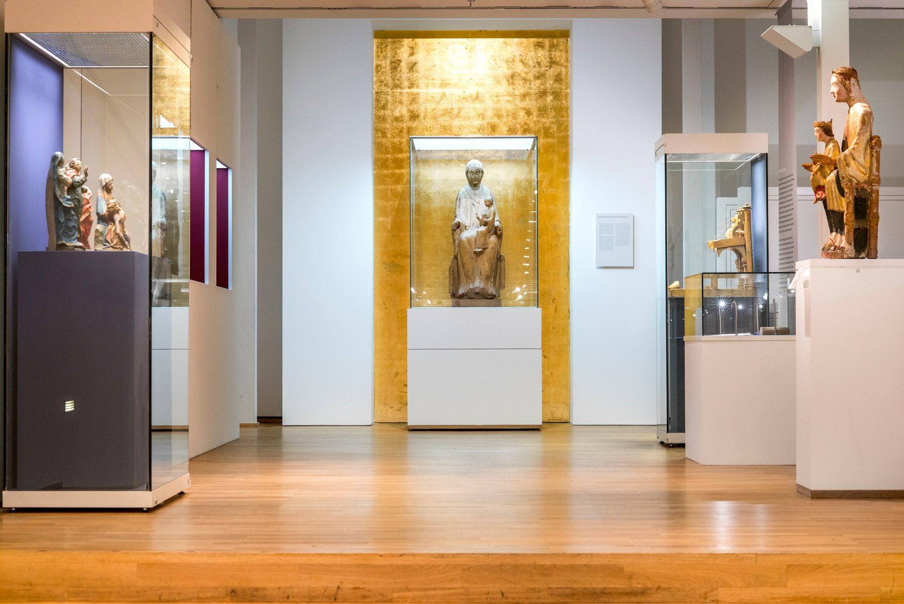 Die Madonna.  Die Skulpturensammlung umfasst neben mittelalterlichen Werken auch herausragende Beispiele westfälischer Barockskulptur wie den Liborischrein von 1627 aus dem Paderborner Dom. Sicherlich die bedeutendste Skulptur ist die vom Paderborner Bischof Imad gestiftete und nach ihm benannte Imad-Madonna (1051–1058, im Bild), eine der ältesten Darstellungen der thronenden Madonna in der abendländischen Kunst.