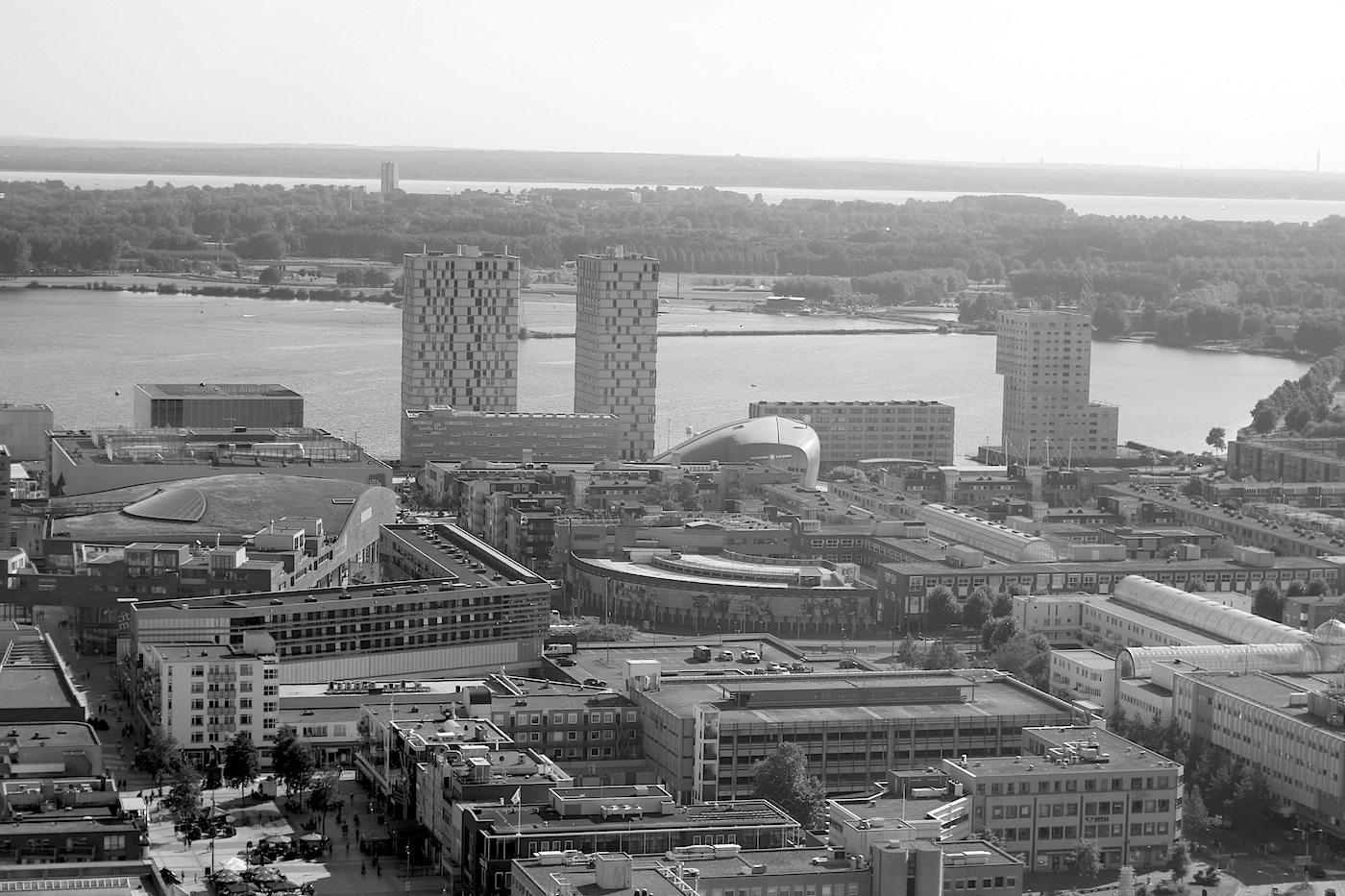 """Stadt mit Skyline. Die zwei im rechten Winkel zueinander stehenden 70 Meter hohen Wohntürme heißen treffend """"Side by Side"""" und wurden von de Architekten Cie und Frits van Dongen entworfen. Fertigstellung 2007."""