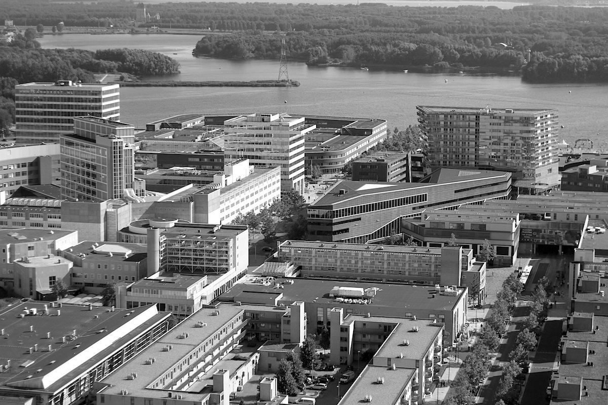 """Stadt mit Klarheit. Links das Rathaus, daneben in der Keilform, das dem Bau die dynamische Schiffsform gibt: De Nieuwe Bibliotheek. Das Heck der Schiffsbücherei wird von """"De Smaragd"""" gestützt."""