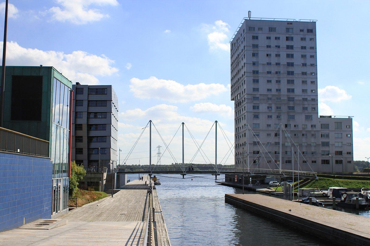 Hengelostraat. Mit Blick auf Weerwater und den Wohnturm Silverline von Claus en Kaan Architecten, 2001. Die filigrane Brücke, die Fietsbrug Olstgracht, ist vom The Wave-Architekten van Zuuk entworfen. Fertigstellung 2003.