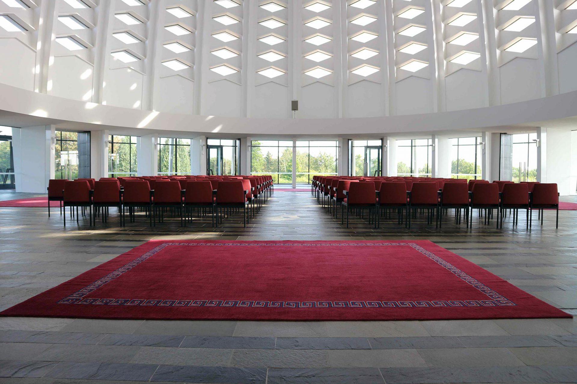 Der Gebetsraum. Die Gebetsrichtung der Pflichtbetenden und somit häufig auch die Ausrichtung der Bestuhlung ist durch die Lage zum Wallfahrtsort Akkon in Westgaliläa bestimmt. Dort starb der Religionsbegründer Baha'ullah 1892.