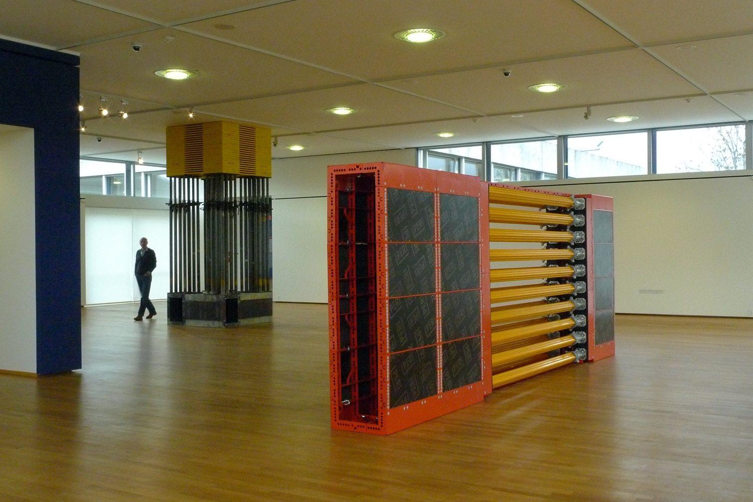 Grundkredit Saar. (Hintergrund) 2012, Stahl, Holz, Gummi, 399 x 150 x 150 cm. Vordergrund: Hochkant 90/09/12 Saar PERI, 2012. 220 x 600 x 55 cm, Saarland Museum, Moderne Galerie.