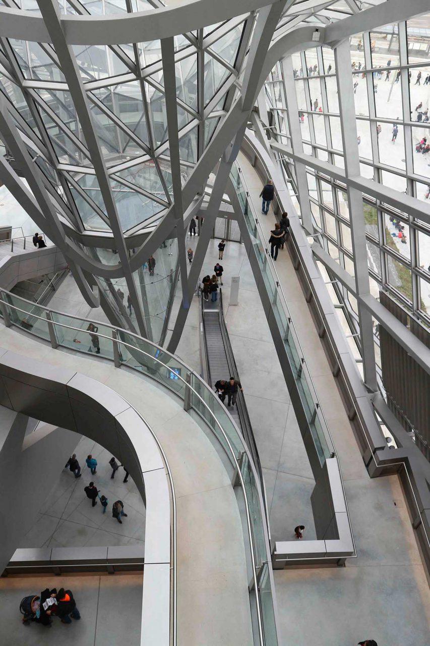 Der Kristall.  Das Eingangsgebäude, der Kristall, ist frei durchgängig und eine vertikale Erschließung der Ausstellungsräume. Über eine Rolltreppe, eine Treppe und eine spiralförmige Rampe gelangt man in den Espace liant, eine Verbindungsstraße, an der links und rechts die einzelnen Ausstellungssäle angeordnet sind.