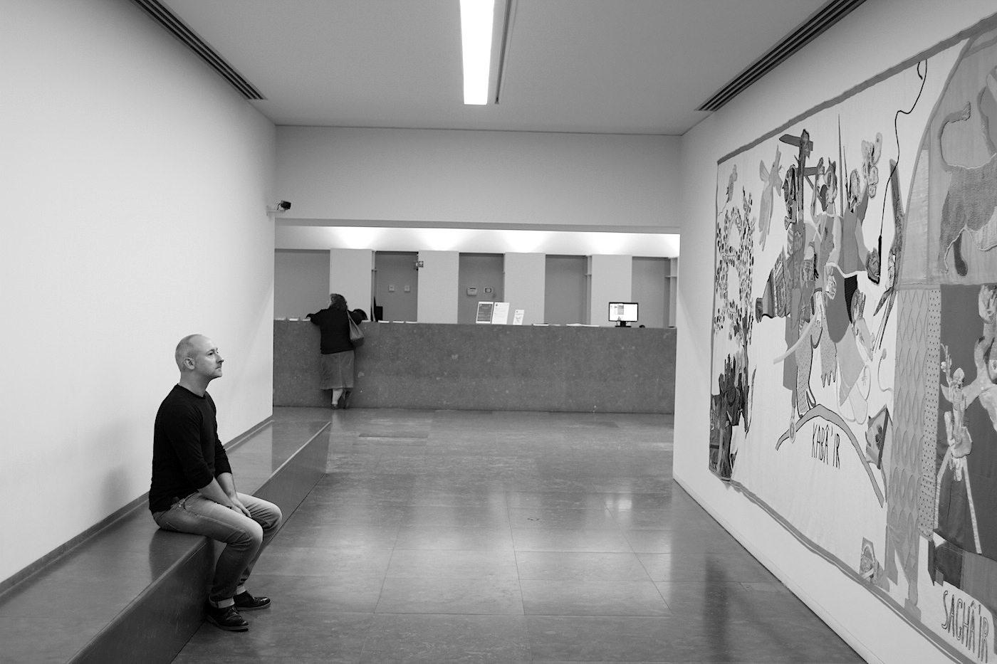 """Haus der Geschichten Paula Rego.  Rechts: die Tapisserie mit 250 x 650 cm-Größe zeigt das von Paula Rego erschaffene """"Battle of Alcáer-Quibir, 1966"""". Links: Tapisserie-Betrachter und Architekt Hendrik Bohle."""