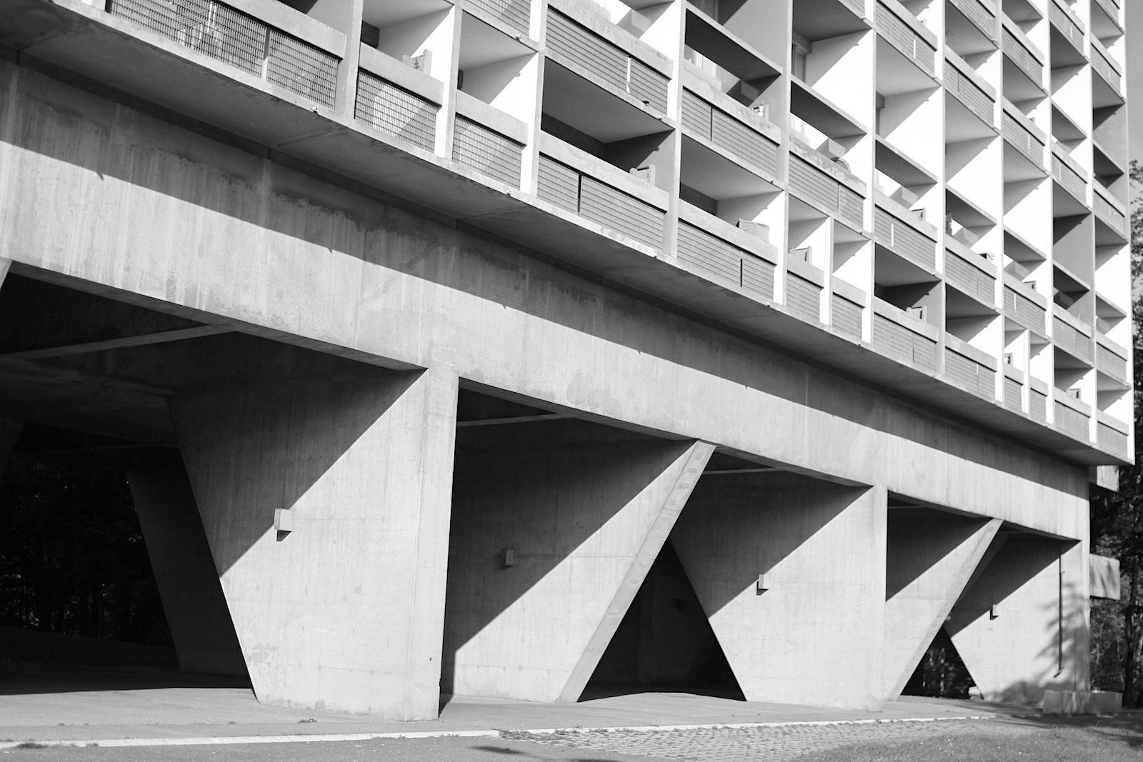 Unité d'Habitation. Der Skelettbau aus Stahlbeton hat 20 Geschosse. Anstelle des Erdgeschosses befindet sich ein Freigeschoss mit Stützen, die das Gebäude tragen.