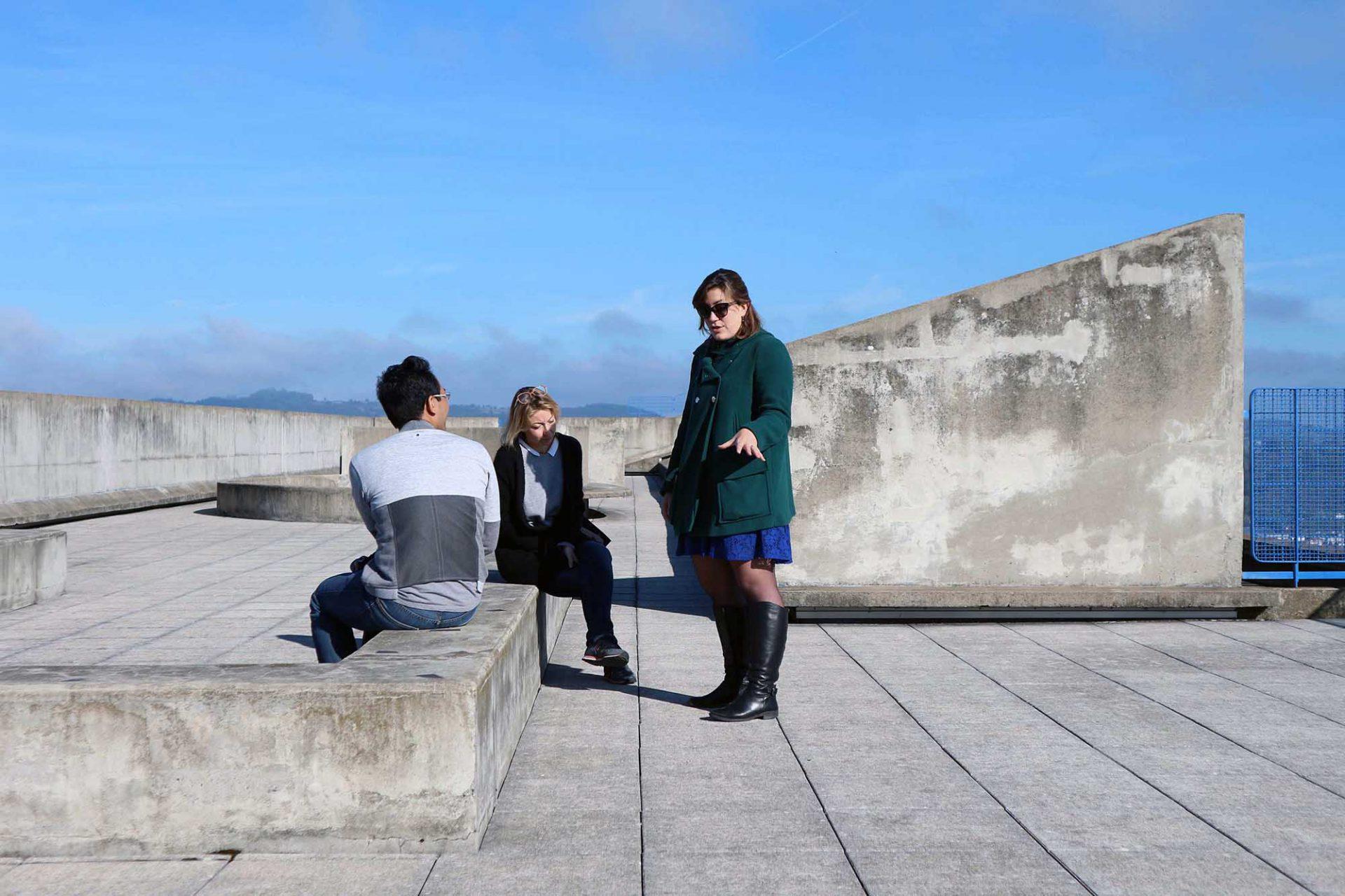 Unité d'Habitation. Wo Betongrau in allen Schattierungen dominiert, befand sich der Spielplatz der Schule. Jan Dimog (li.) im Gespräch mit Site Le Corbusier-Repräsentantin Maelle Braquet (stehend) und Sophie Vaissellet von Auvergne-Rhône-Alpes Tourisme.
