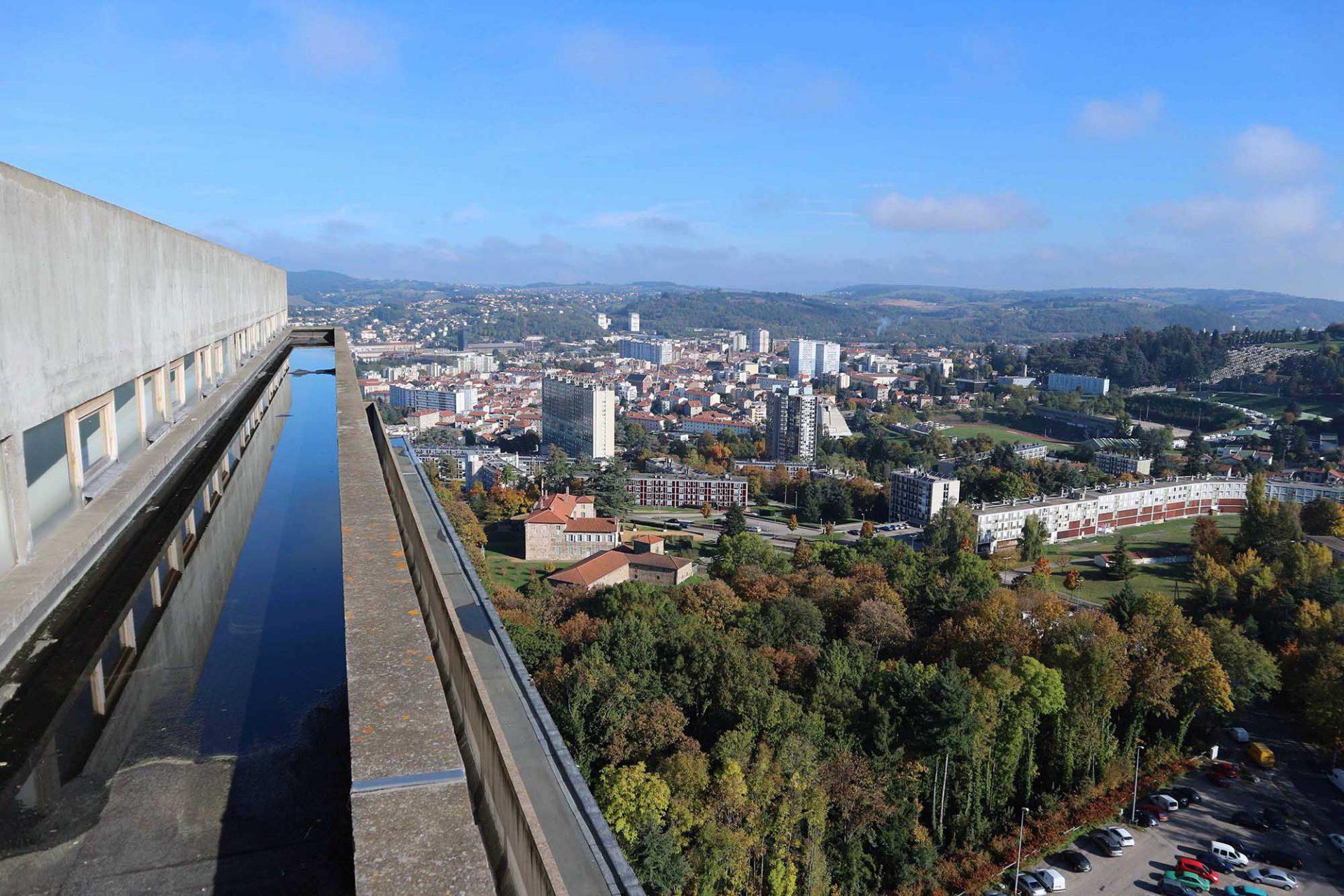 """Weite. Der Blick vom Dach der Unité d'Habitation auf Firminy-Vert und Firminy. Der von der Moderne begeisterte Bürgermeister Eugène Claudius-Petit engagierte Le Corbusier mit einem Team von Architekten für den Bau von mehreren Projekten und die Stadtplanung von Firminy-Vert. Hier sollte das """"grüne Firminy"""" ab den 1950er-Jahren mit den Le Corbusier-Vorstellungen des menschlichen Wohnens entstehen."""