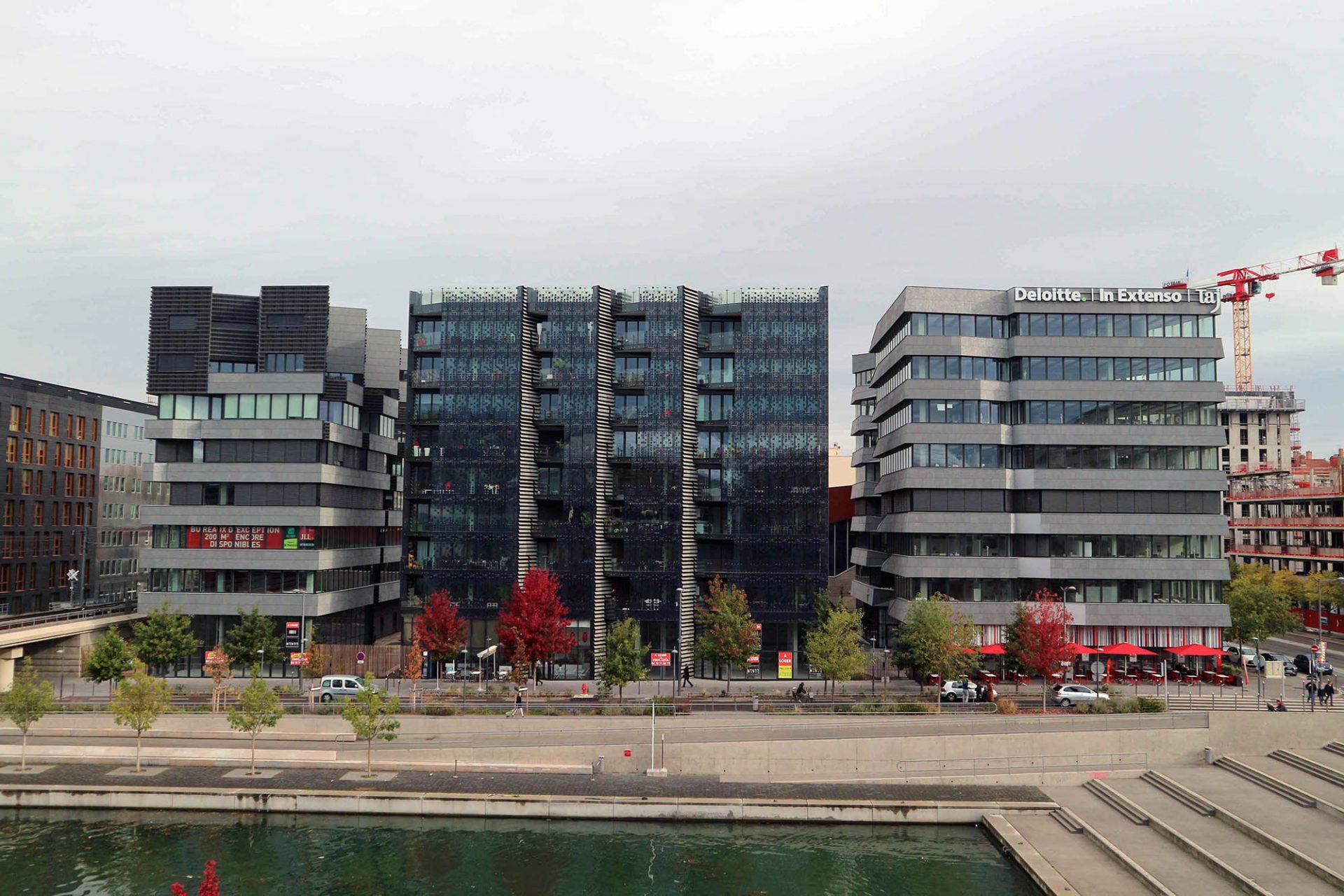 Quai Antoine Riboud.  Material- und Formenmischung am Bassin: das Wohnhaus in der Mitte mit der halbtransparenten Solarfassade produziert mehr Energie, als die Bewohner verbrauchen.