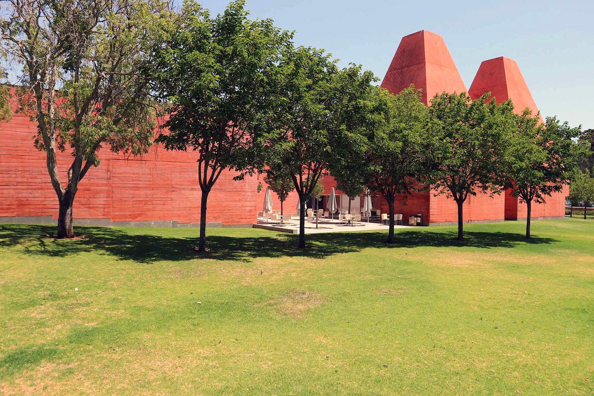 """Haus der Geschichten Paula Rego.  """"Die Verteilung der Körper erfolgte wie ein Abdruck eines Negativbildes, das sich außerhalb der Durchmesser der Baumwipfel ergibt. Dieses """"Yang""""- und """"Yin""""-Spiel, zwischen künstlich Geschaffenem und der Natur half mir auch bei der Entscheidung für roten Beton als Außenmaterial – die Kontrastfarbe zum Grün der Bäume."""" – Eduardo Souto de Moura"""