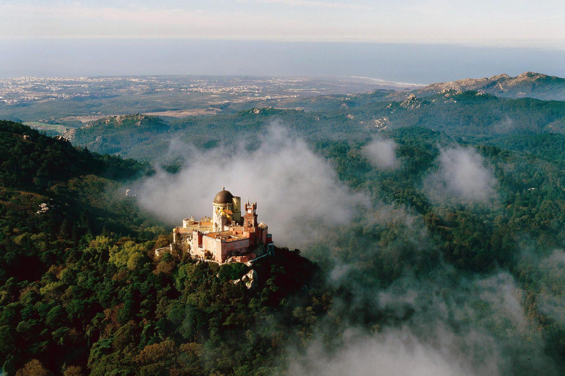 """Magisch.  Der Palácio Nacional da Pena thront auf dem """"Berg des Mondes"""" und überblickt die saftig grüne Kulturlandschaft bis hin zum Atlantik."""