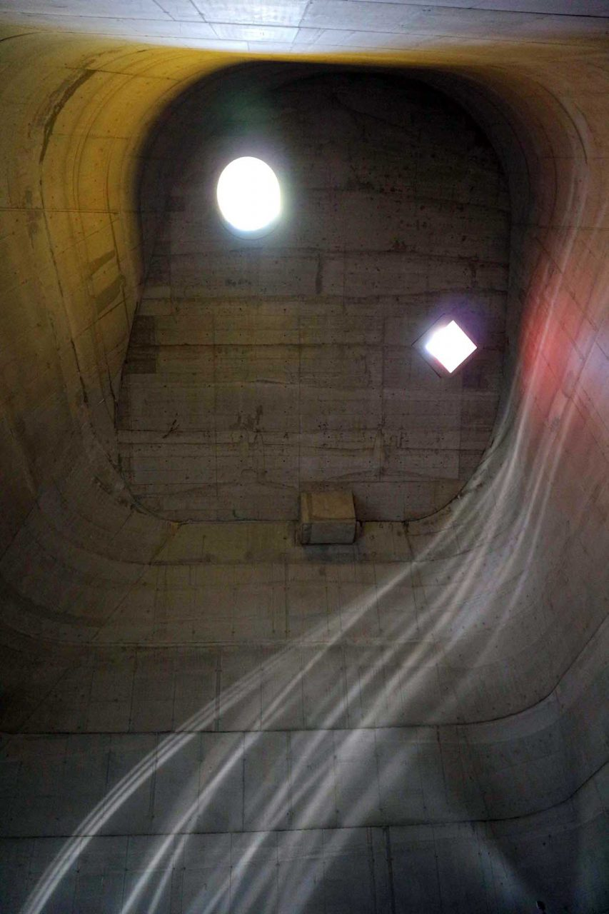 """L'église Saint-Pierre.  Auf dem Dach lenken quadratische und runde """"Lichtkanonen"""" die Strahlen der Sonne ins Innere des Konus."""