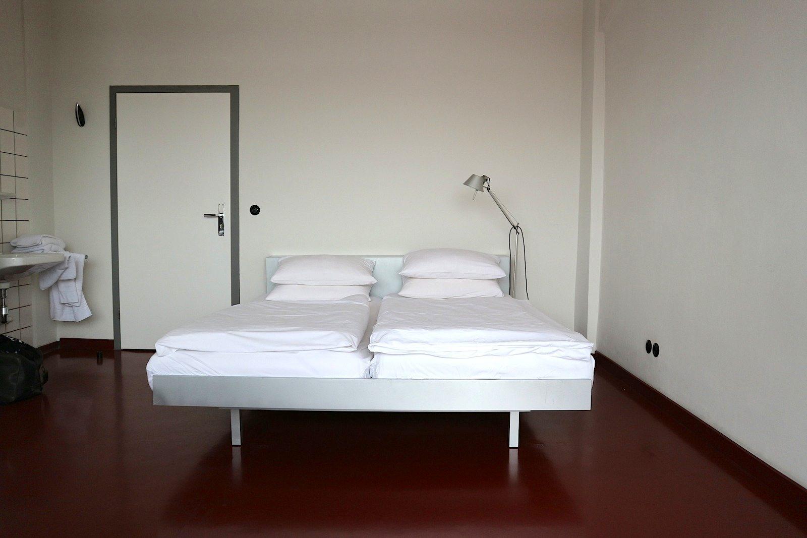 Konzentration. Ein Bett, eine Nachttischlampe, Decken und Kissen. Mehr ...