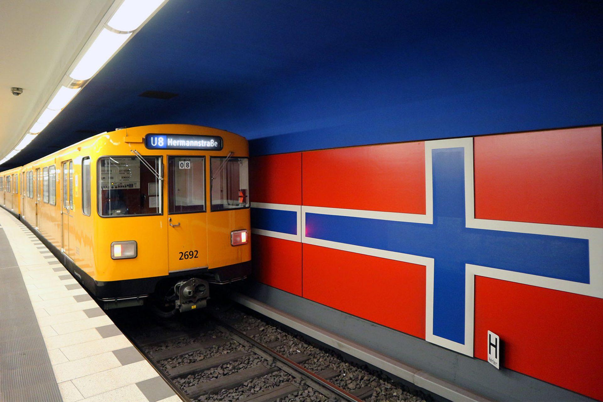 Osloer Straße. Heute durchgehend weiß beschichtet, waren die Decken der Bahnsteige ursprünglich unterschiedlich in gelb und blau gehalten. Nüchterne Metall-Paneele bekleideten die Wände. Heute hängt hier dunkelblaue Emaille.