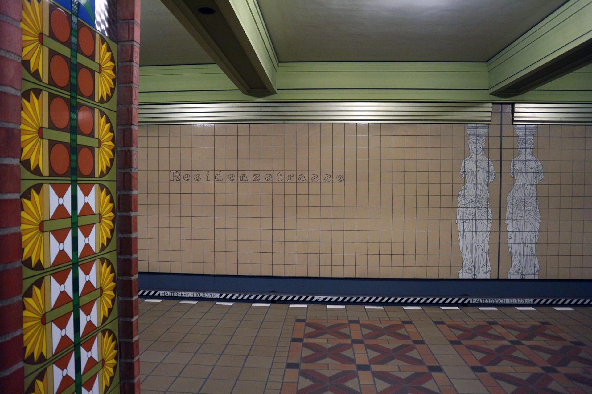 Residenzstraße. Die Station soll an die ehemalige Residenzstadt Berlin erinnern. Pläne des Stadtschlosses und Statuen zieren die hell gehaltenen Wände. Die Stützen hingegen sind bunt gekachelt. Ein Verweis auf das bunte Knüpfwerk der Preußen-Residenz.