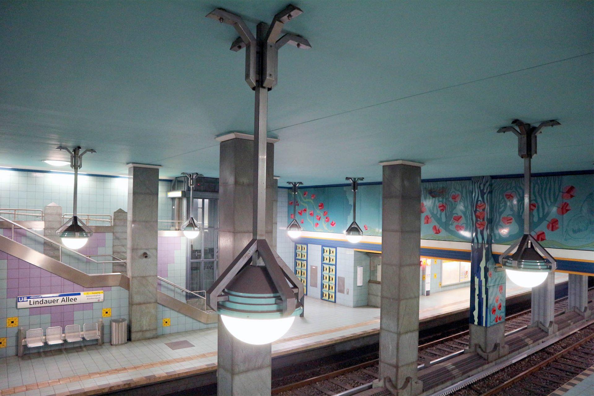 Lindauer Allee. Der türkis gehaltene Bahnhof ist der Einzige mit einer umlaufenden Galerie. Noch eine Besonderheit sind die Schrägseilaufzüge, die einen barrierefreien Zugang ermöglichen.