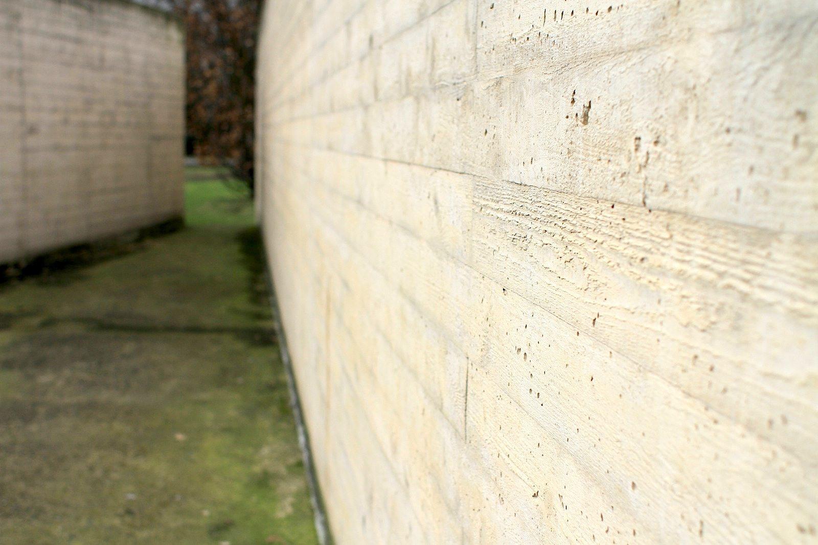 Verletzungen.  Die Oberfläche des Betons wurde nachträglich sandgestrahlt und damit explizit beschädigt. Dadurch wird klar, dass es ein Ort der Verletzungen und Verletzten geht.