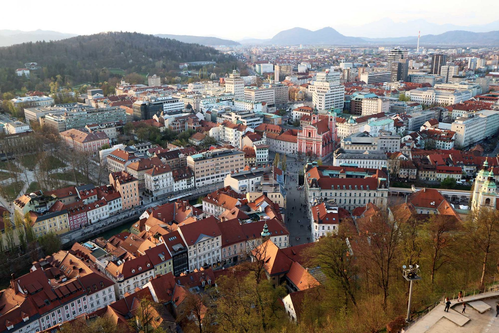 Landachse. Sie verbindet die Burg und Altstadt im Vordergrund über die Drei Brücken mit dem Waldhügel Rožnik und dem Tivolipark im Hintergrund.